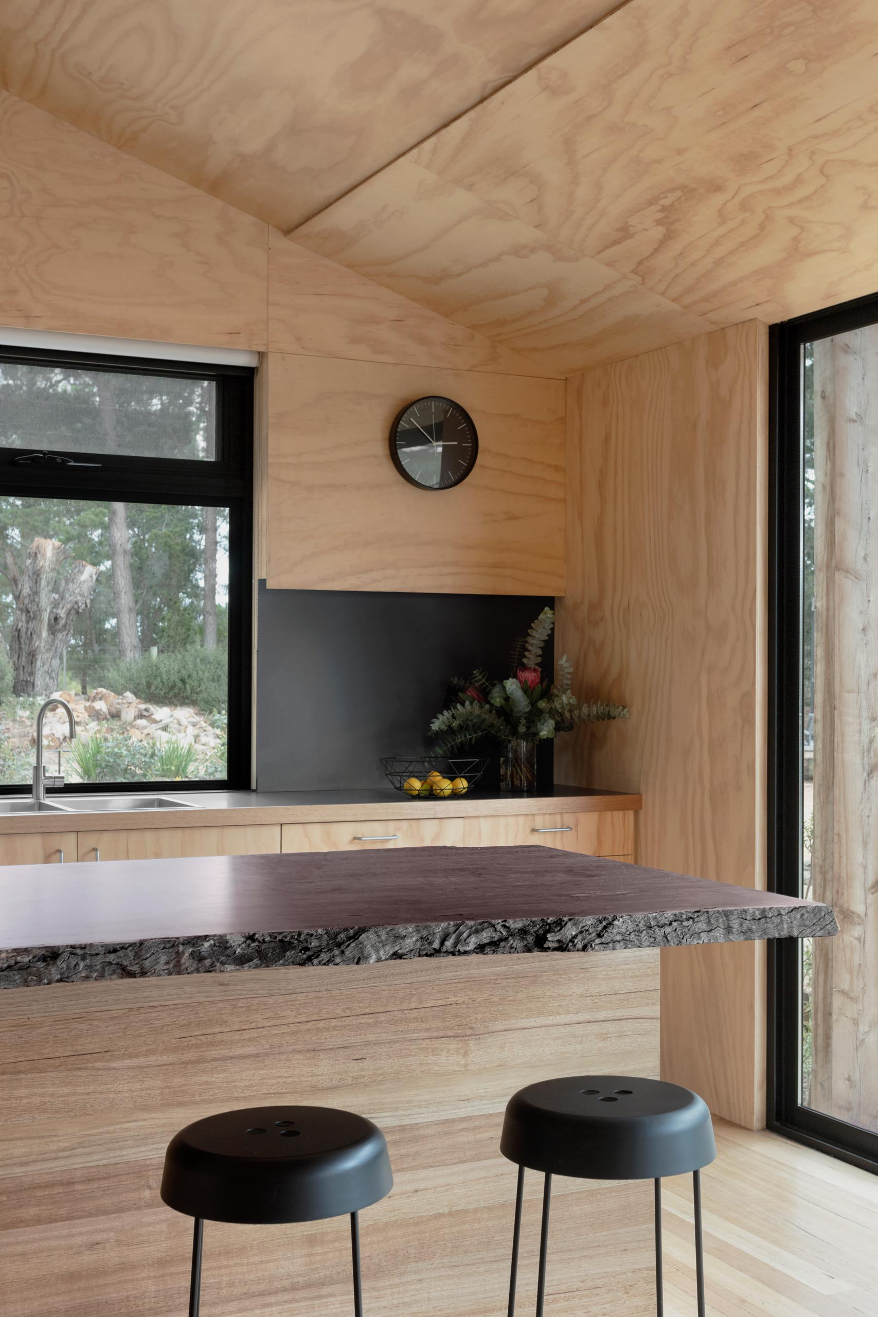 A modern plywood kitchen with a matte black countertop and backsplash, and an island with a live edge wood countertop.