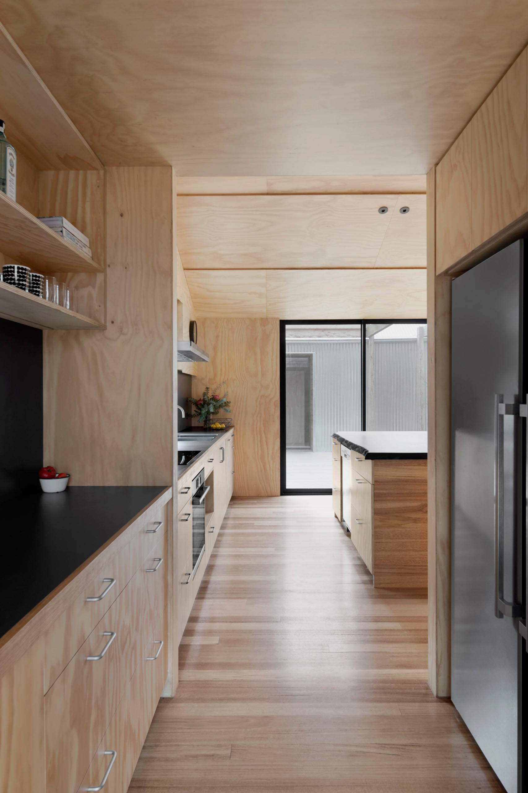 A modern plywood kitchen with a matte black countertop and backsplash, and separate pantry.