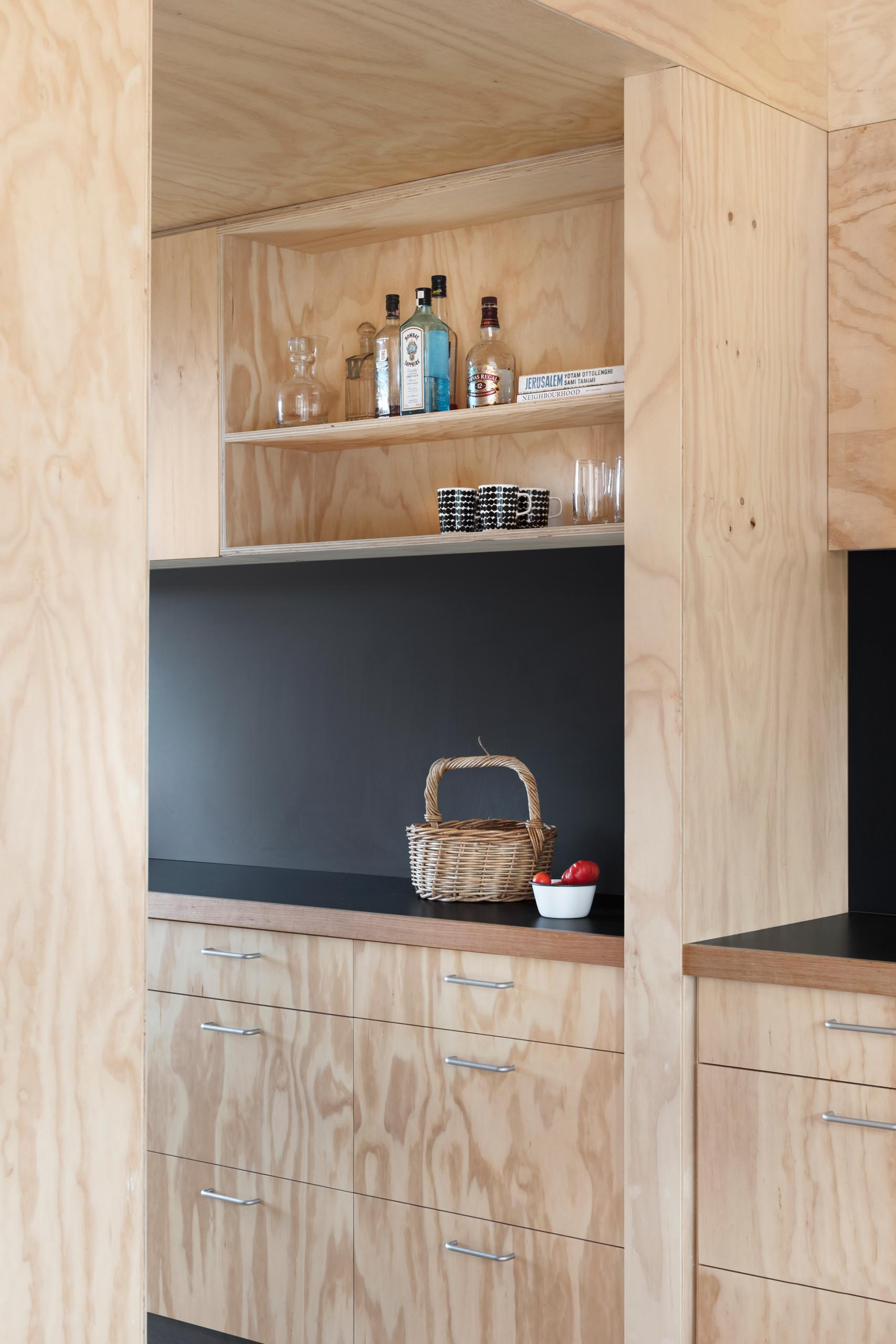 A modern plywood kitchen with a matte black countertop and backsplash.