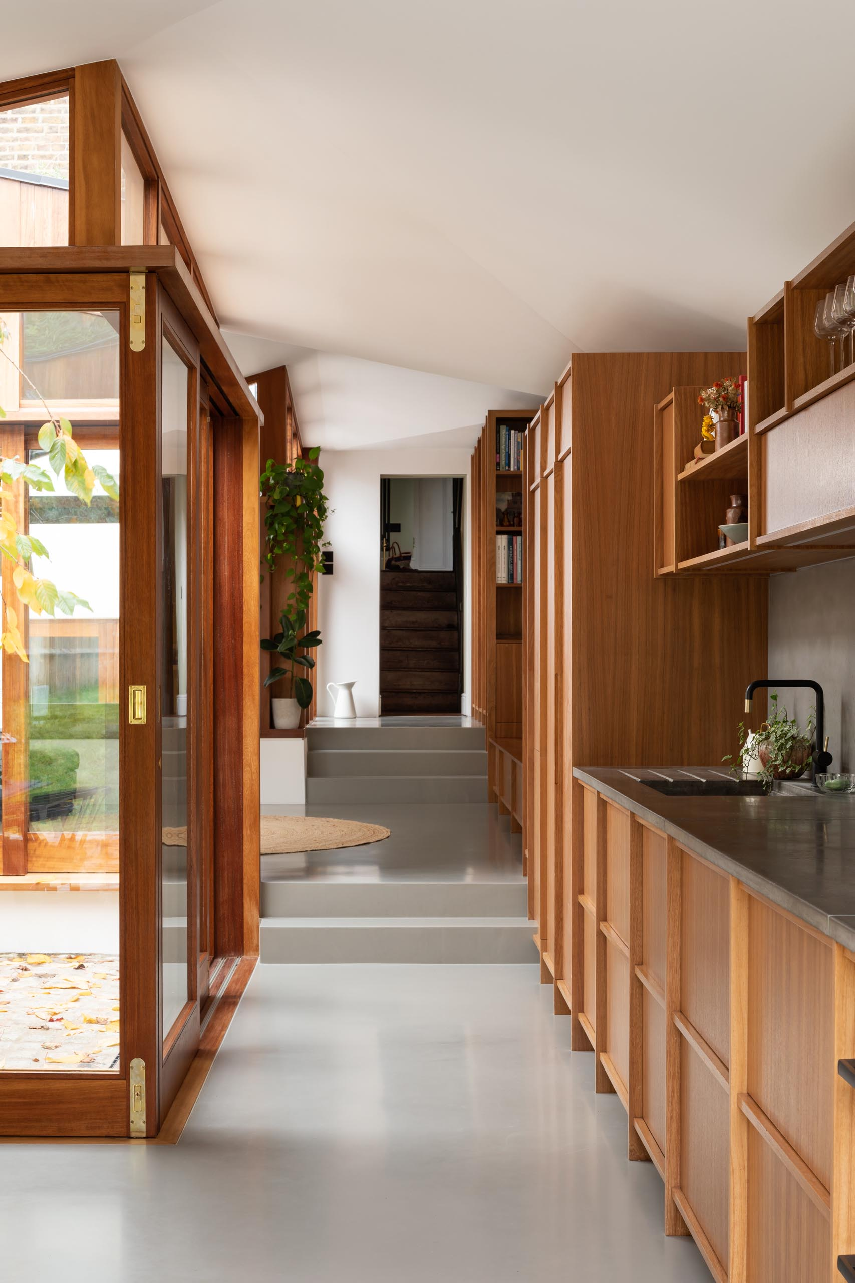 A linear wood kitchen with hardware free cabinets and a dark gray backsplash.