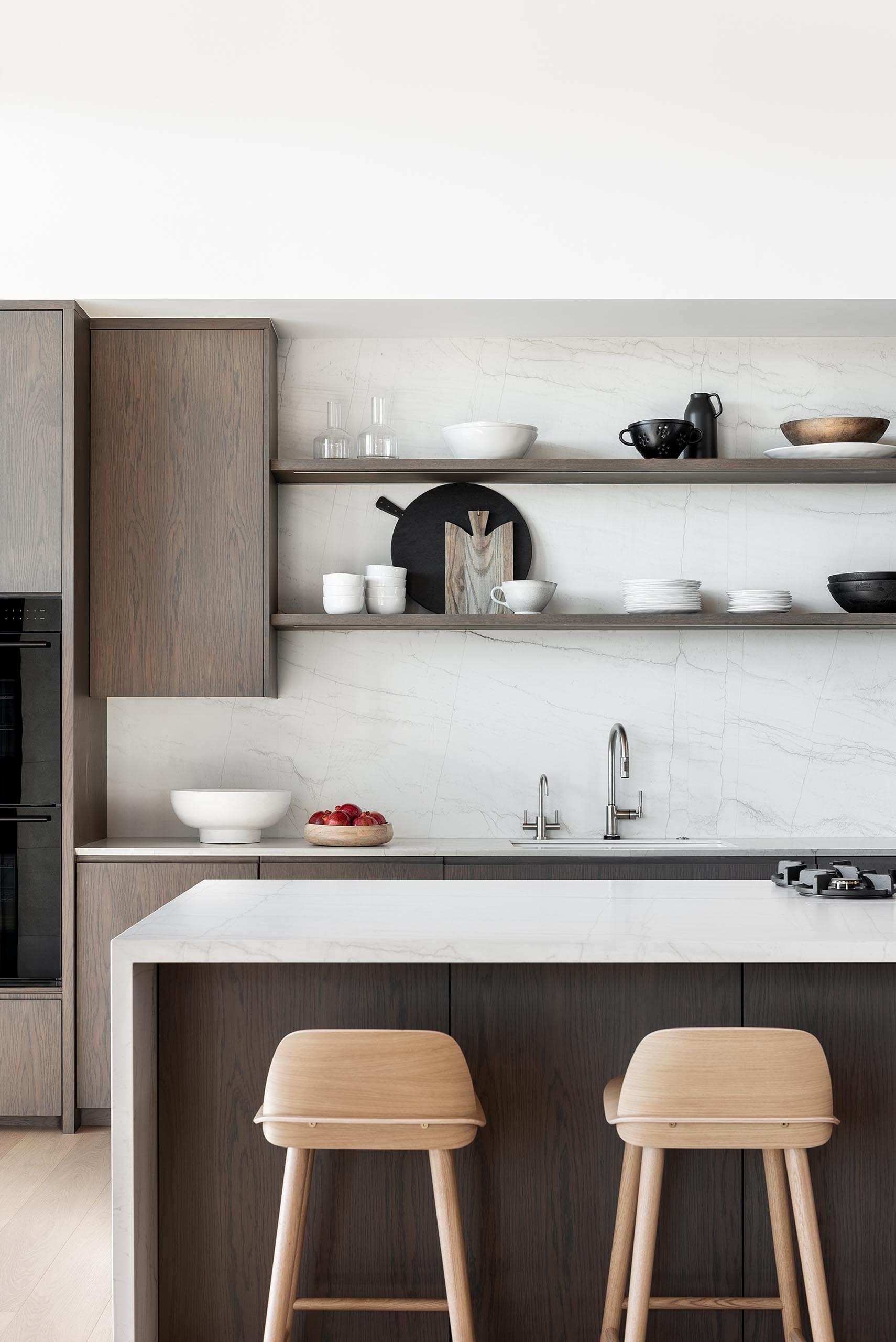 A modern kitchen with wood cabinets, open shelving, and light colored countertops.