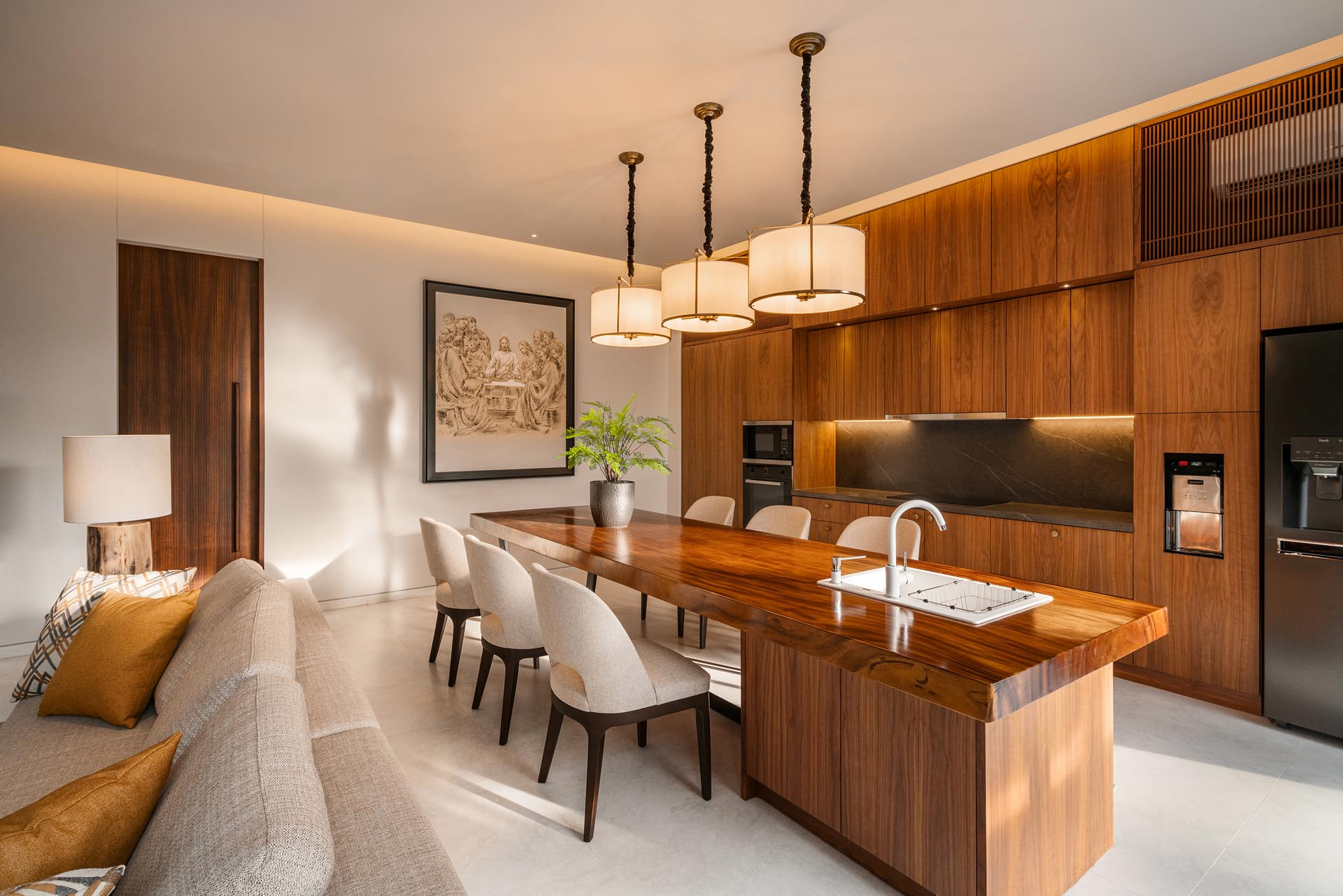 The living room shares the large open plan room with the wood kitchen and dining area, which is incorporated into the design of the kitchen island.