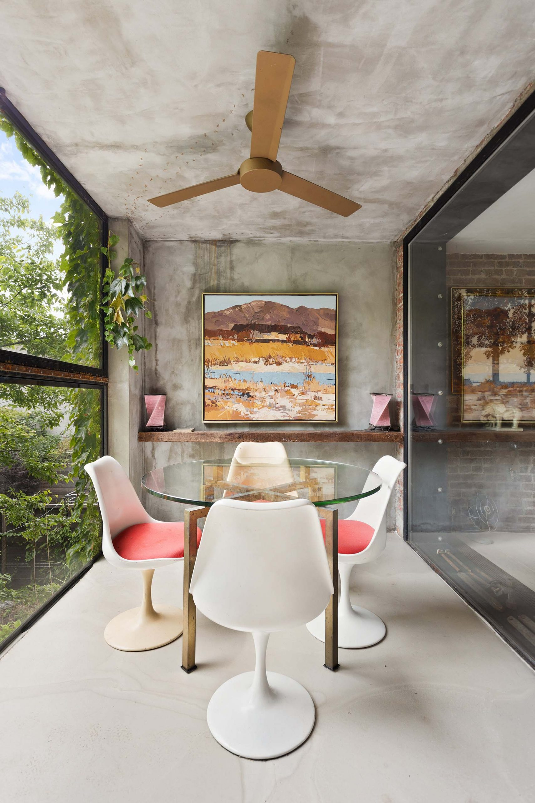 In this modern dining room, raw concrete wraps from the ceiling onto the wall and floor, while the glass walls allow natural light to filter through to the interior of the home.