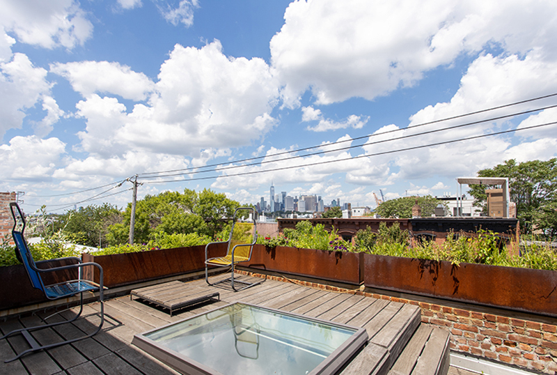 A rooftop deck with weathering steel planters.
