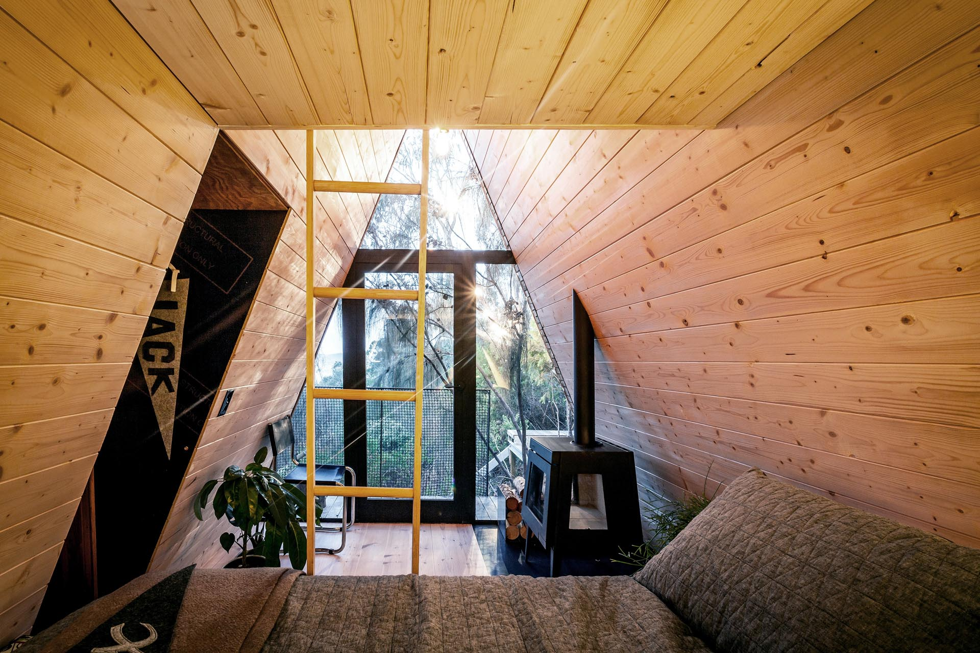 A small and modern wood-lined A-framed cabin with a sleeping area and lofted space.