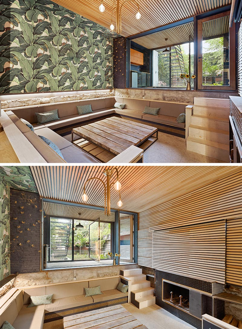 A sunken living room has been created on the lowest level of this home, and includes a wood ceiling that wraps around onto the wall, and extends outside.