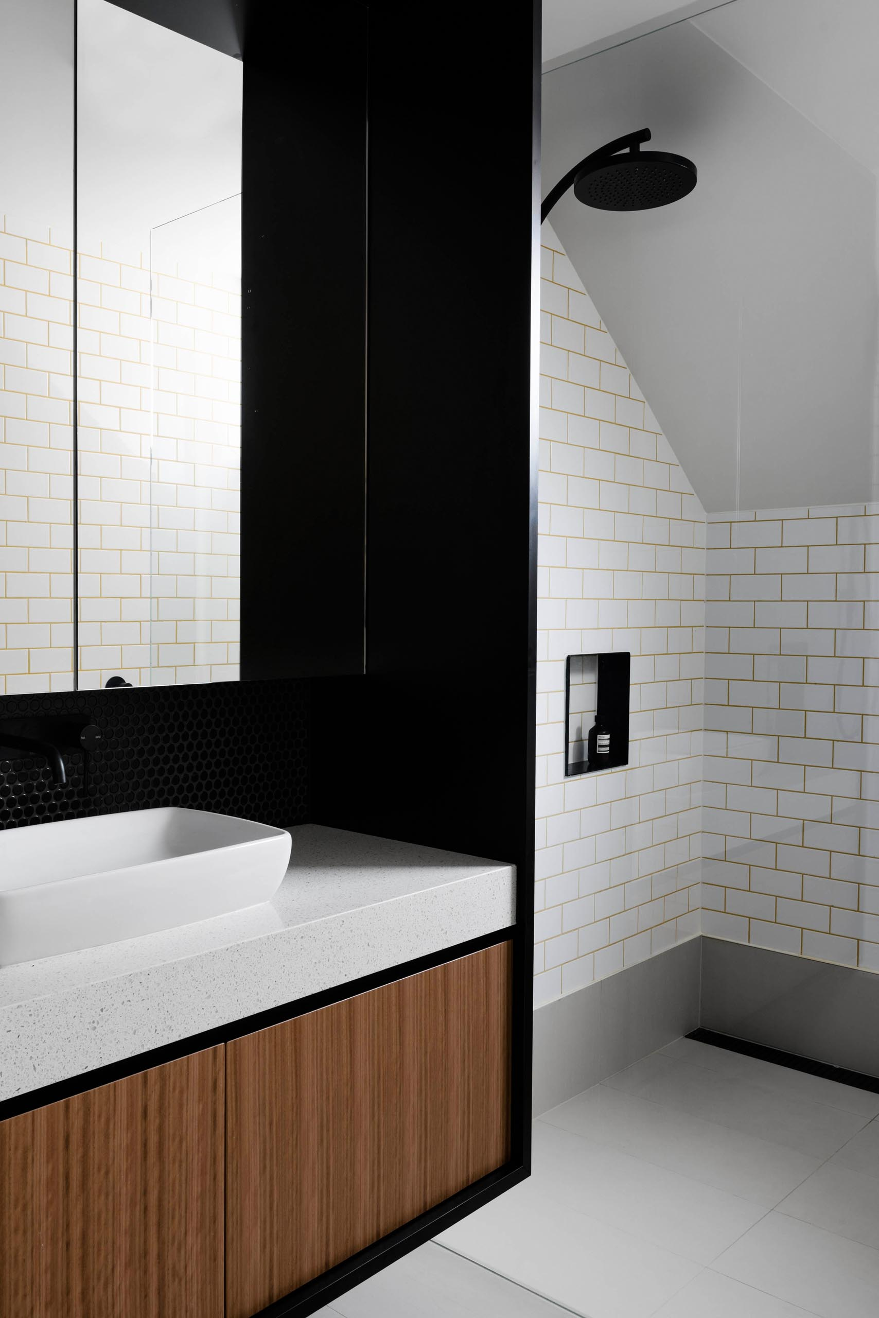 This modern bathroom has a black mirror/vanity surround and black-lined shower niche.