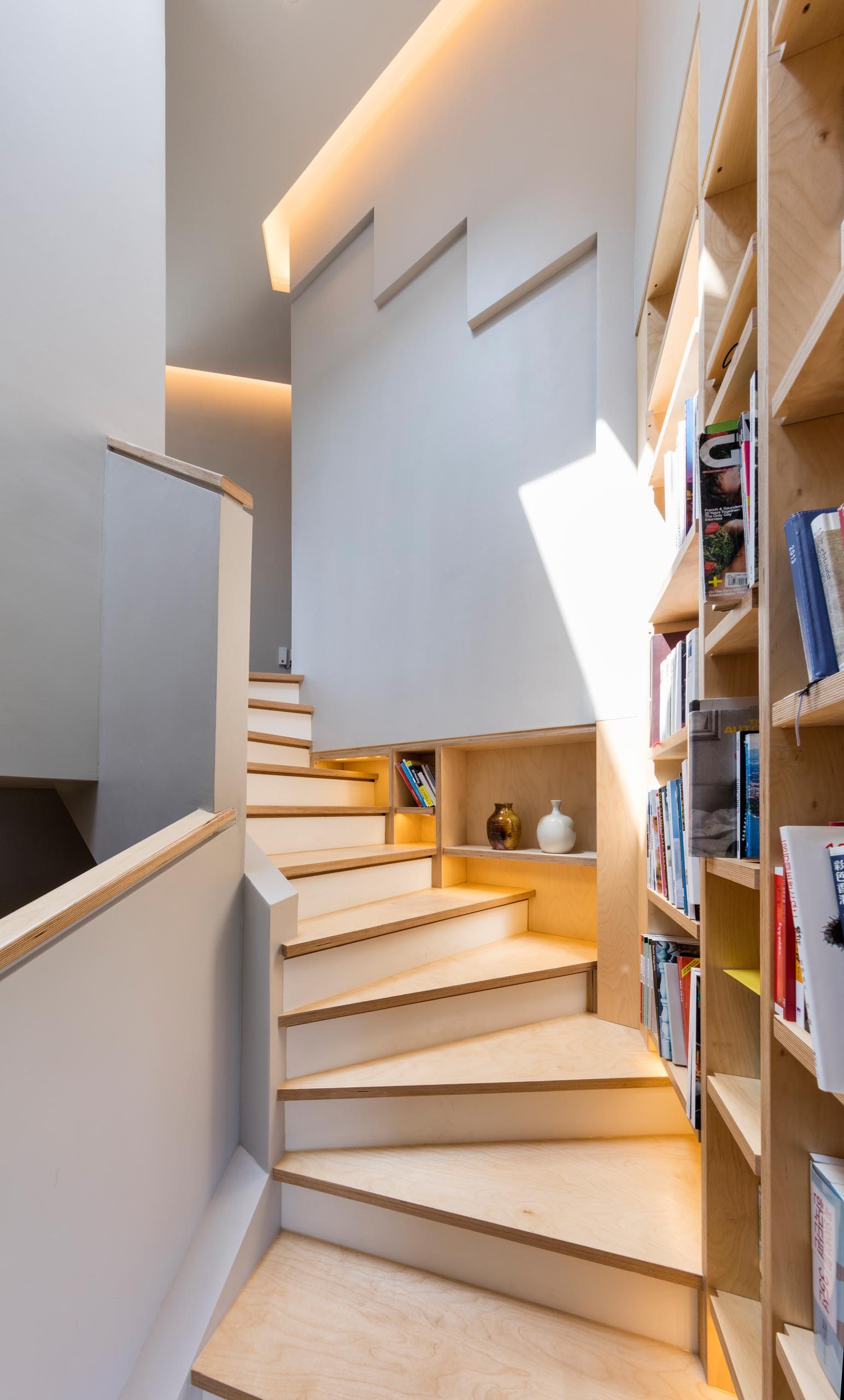 A built-in bookshelf lined with wood that follows the staircase in a modern home.