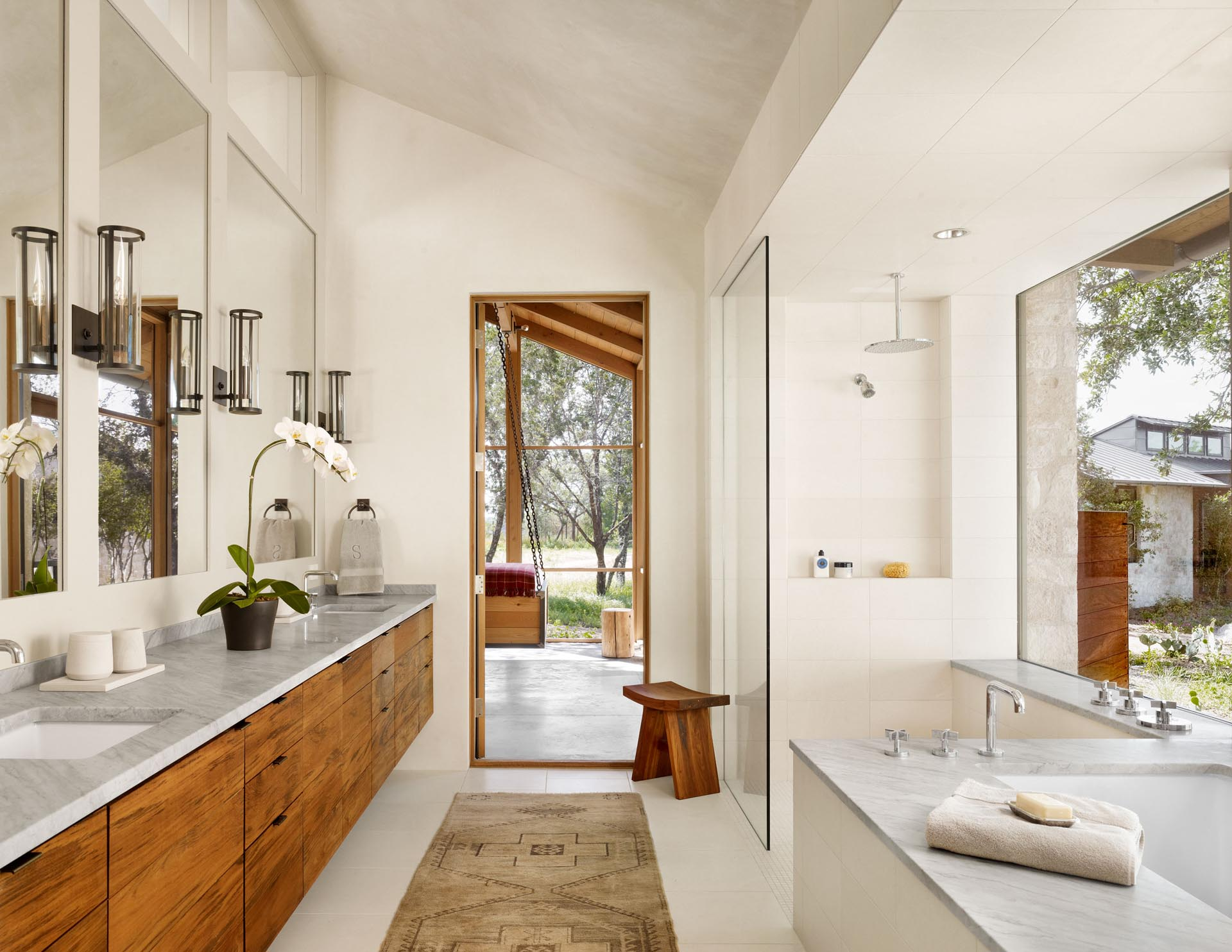 A walk-through bathroom includes a wood vanity that runs the length of the wall, as well as a built-in bathtub and a walk-in shower with an oversized shelving niche.