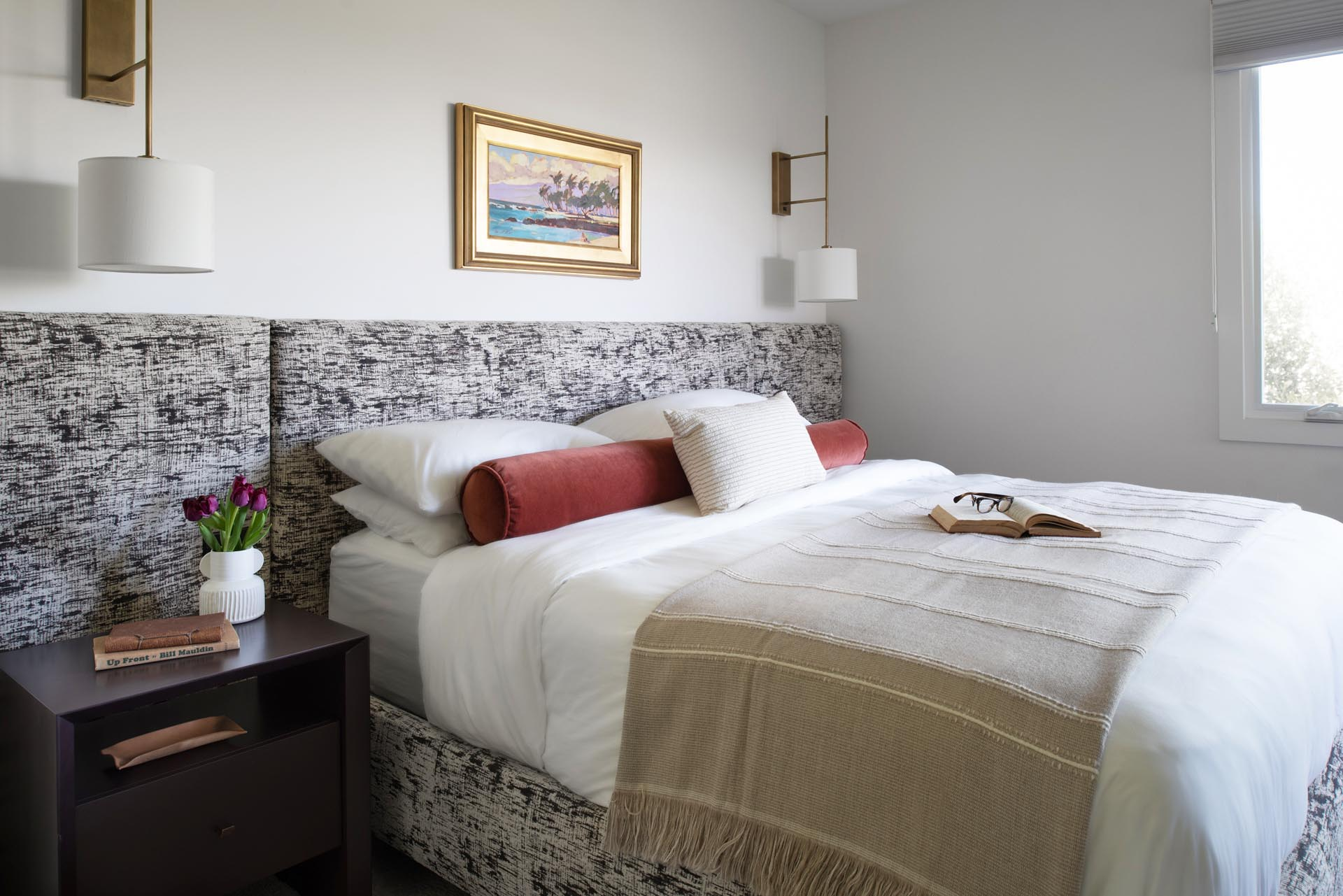 In this primary bedroom, a custom wall to wall headboard in Kelly Wearstler fabric was designed with integrated light switches as well as outlets. The fabric used for the headboard also carries on to the bed frame, while wall lights act as bedside tables.
