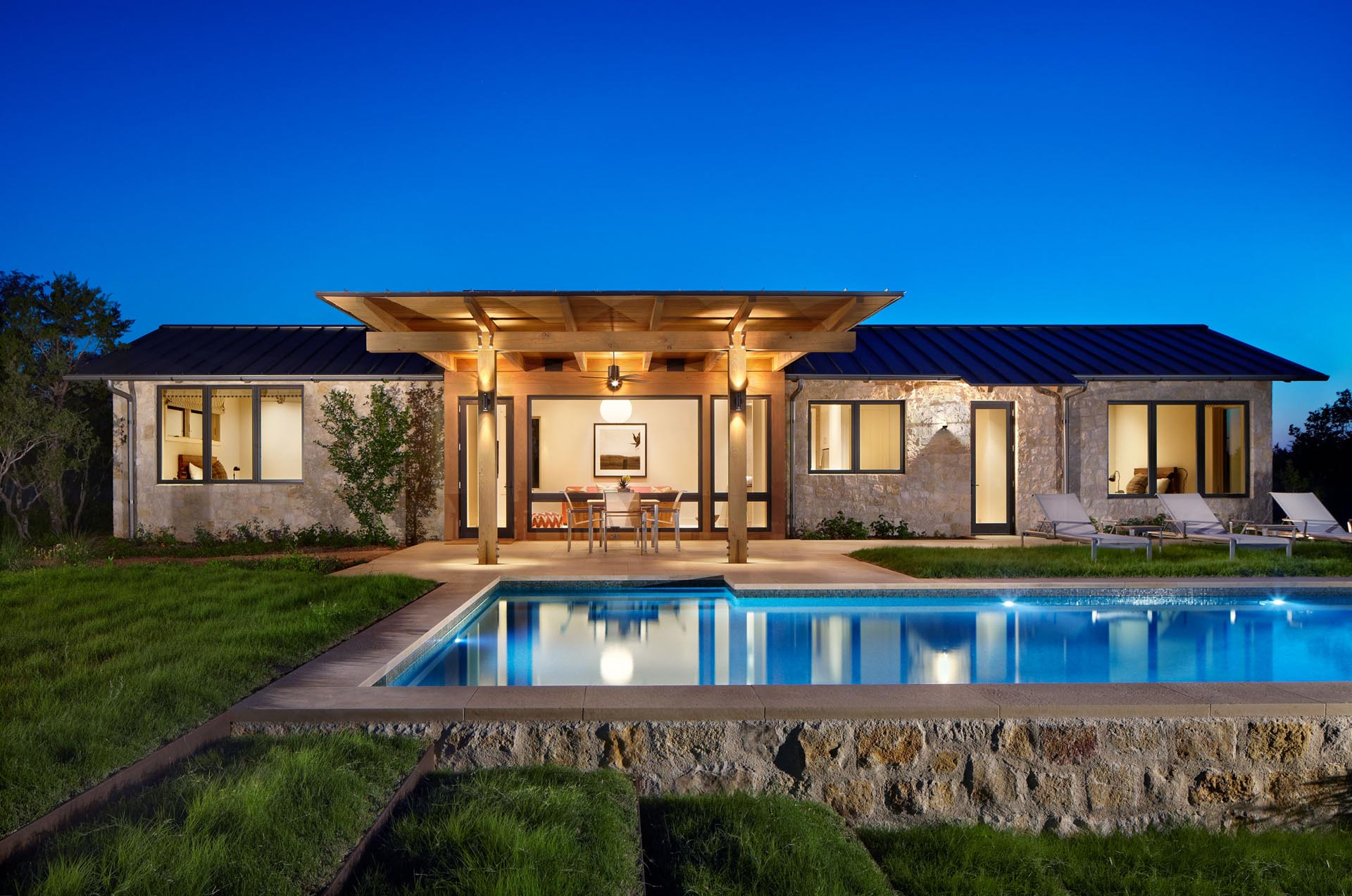 A guest house by the pool the includes a pair of bedrooms and an open plan living room and kitchen.