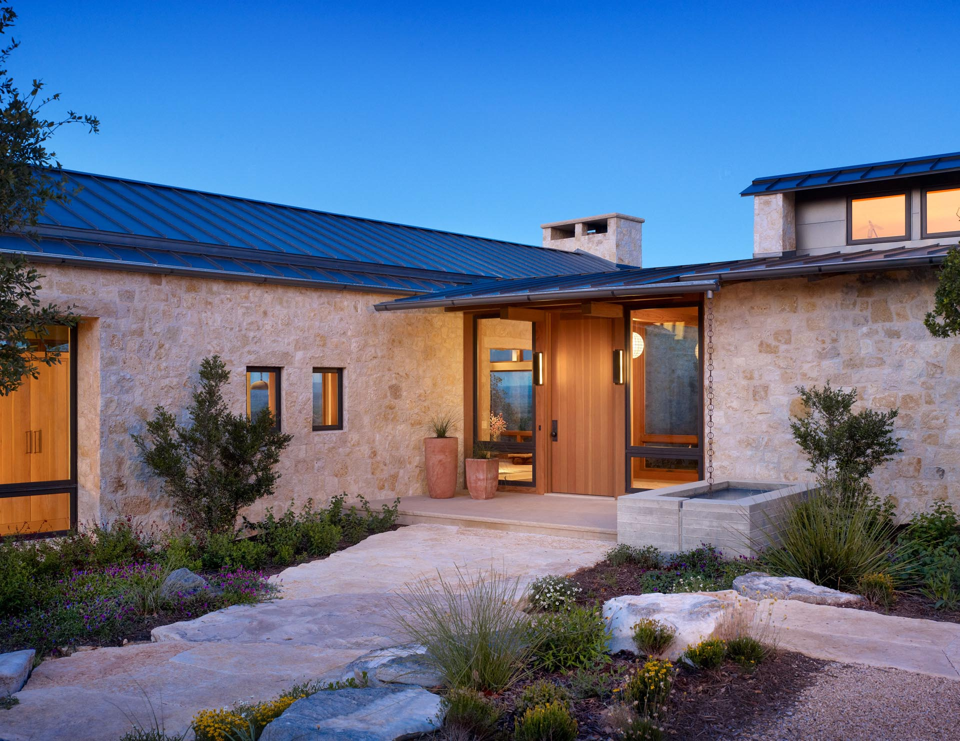 This contemporary home includes limestone walls, a metal roof, black window frames, and a landscaped path to the wood front door.