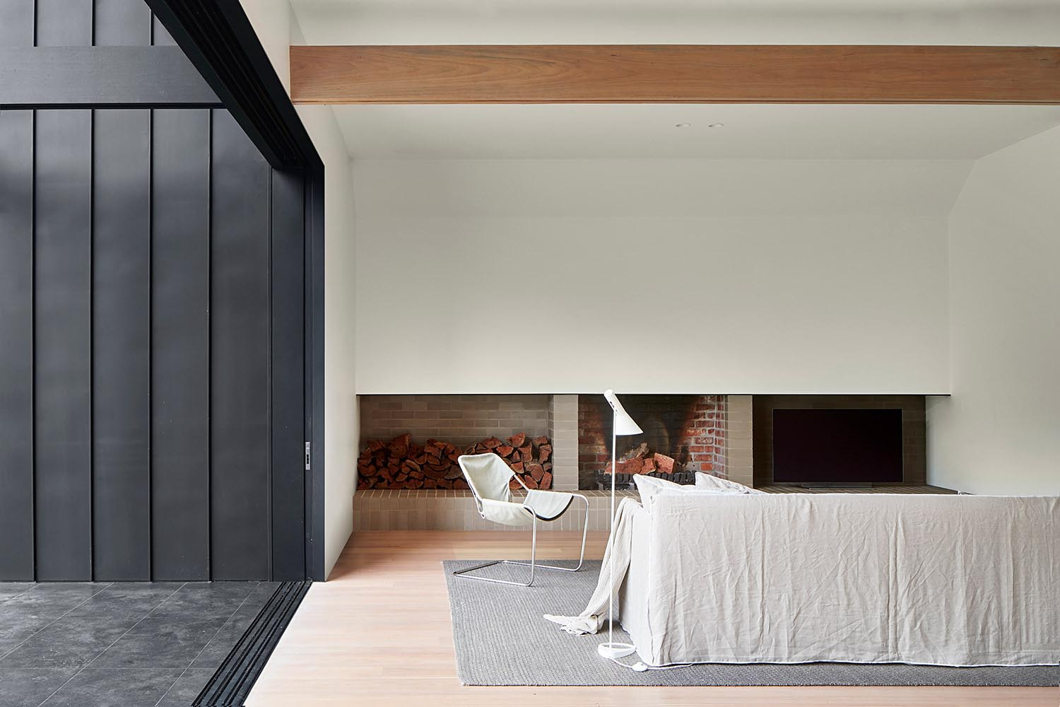 A living room with a modern brick fireplace and firewood storage.