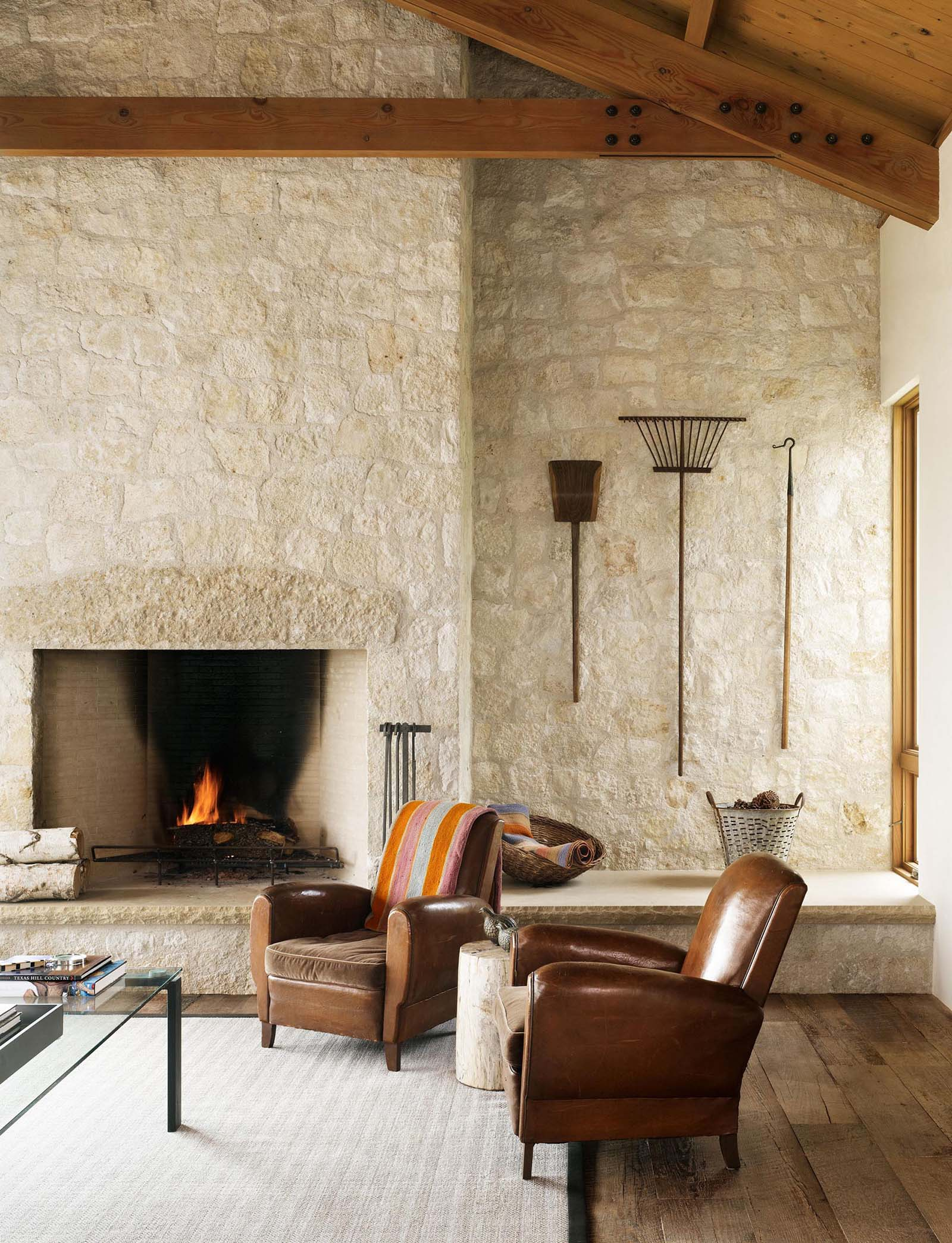 A living room with a limestone wall that surrounds the fireplace.