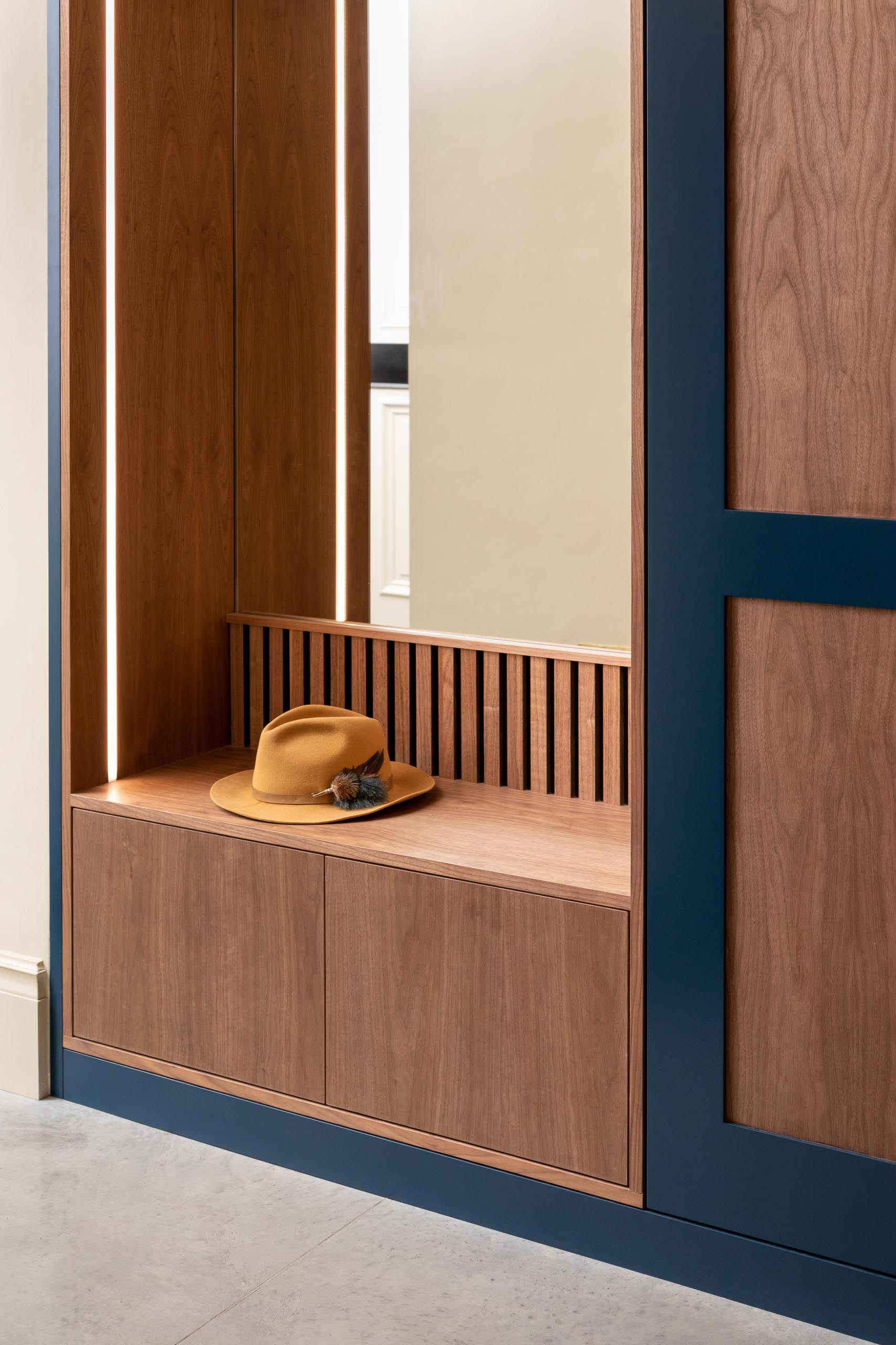 A modern custom designed entryway bench with a mirror, storage, and integrated LED lighting.
