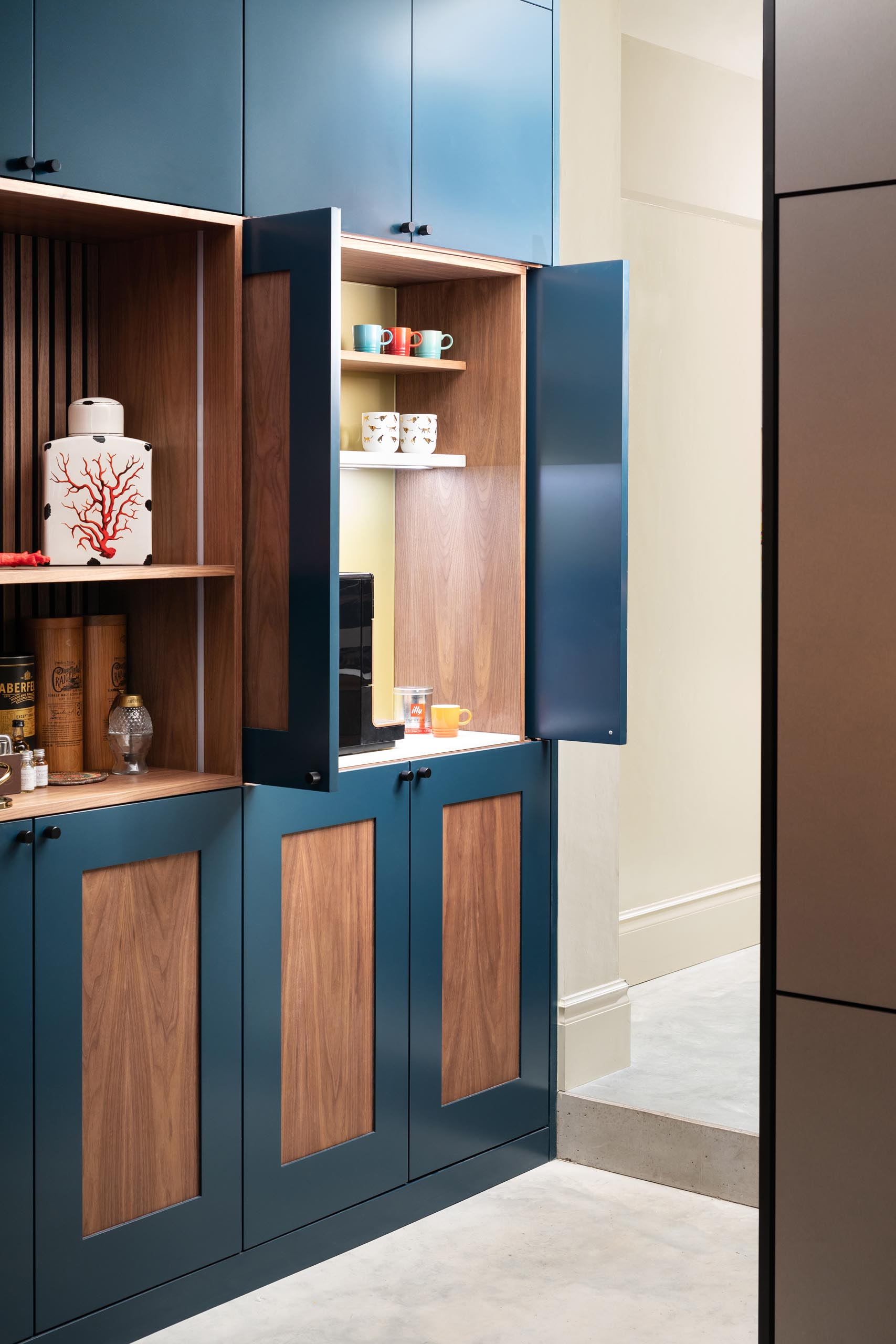 A custom designed cabinet with a coffee station hidden within.