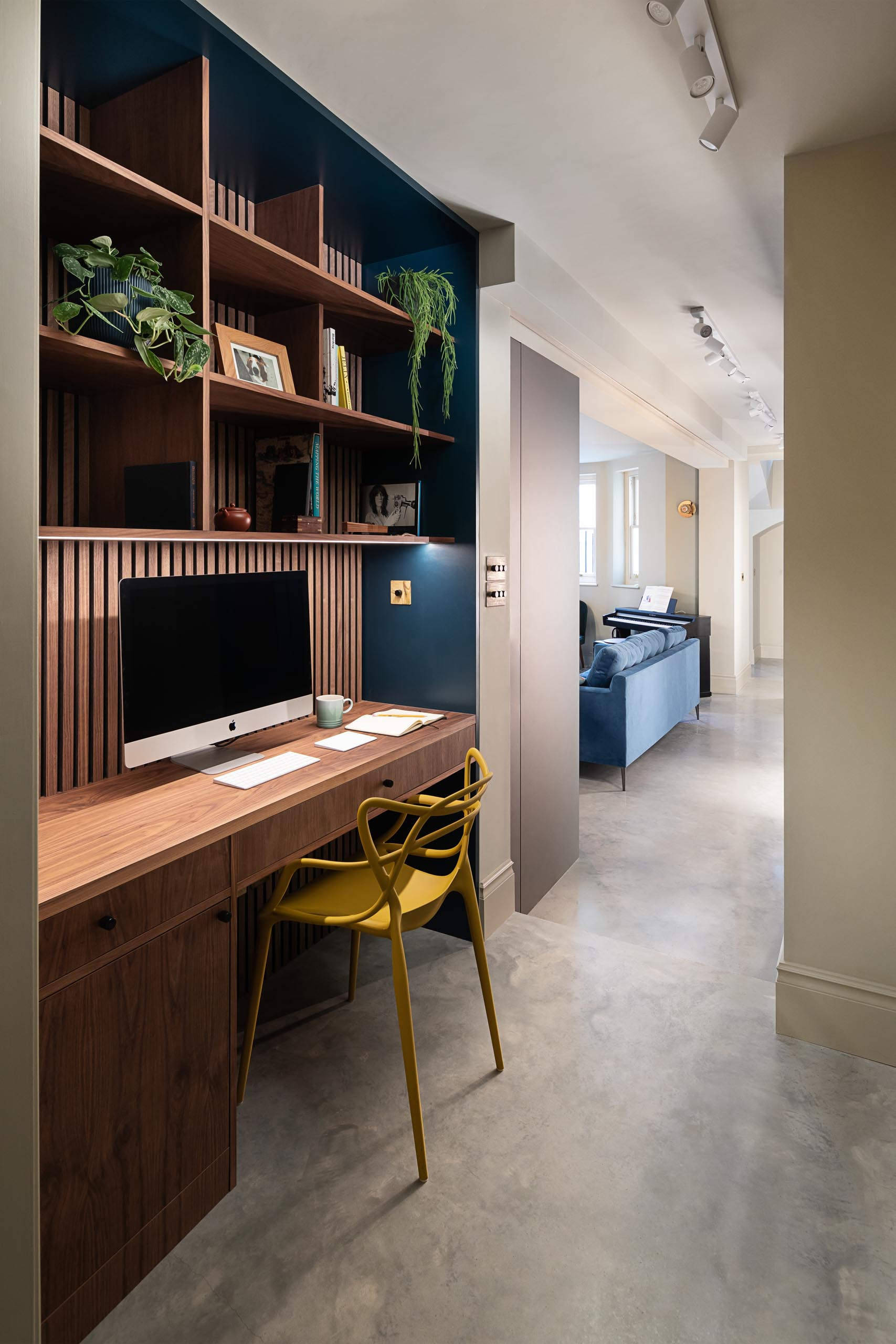 A modern apartment with a custom designed home office in the hallway.