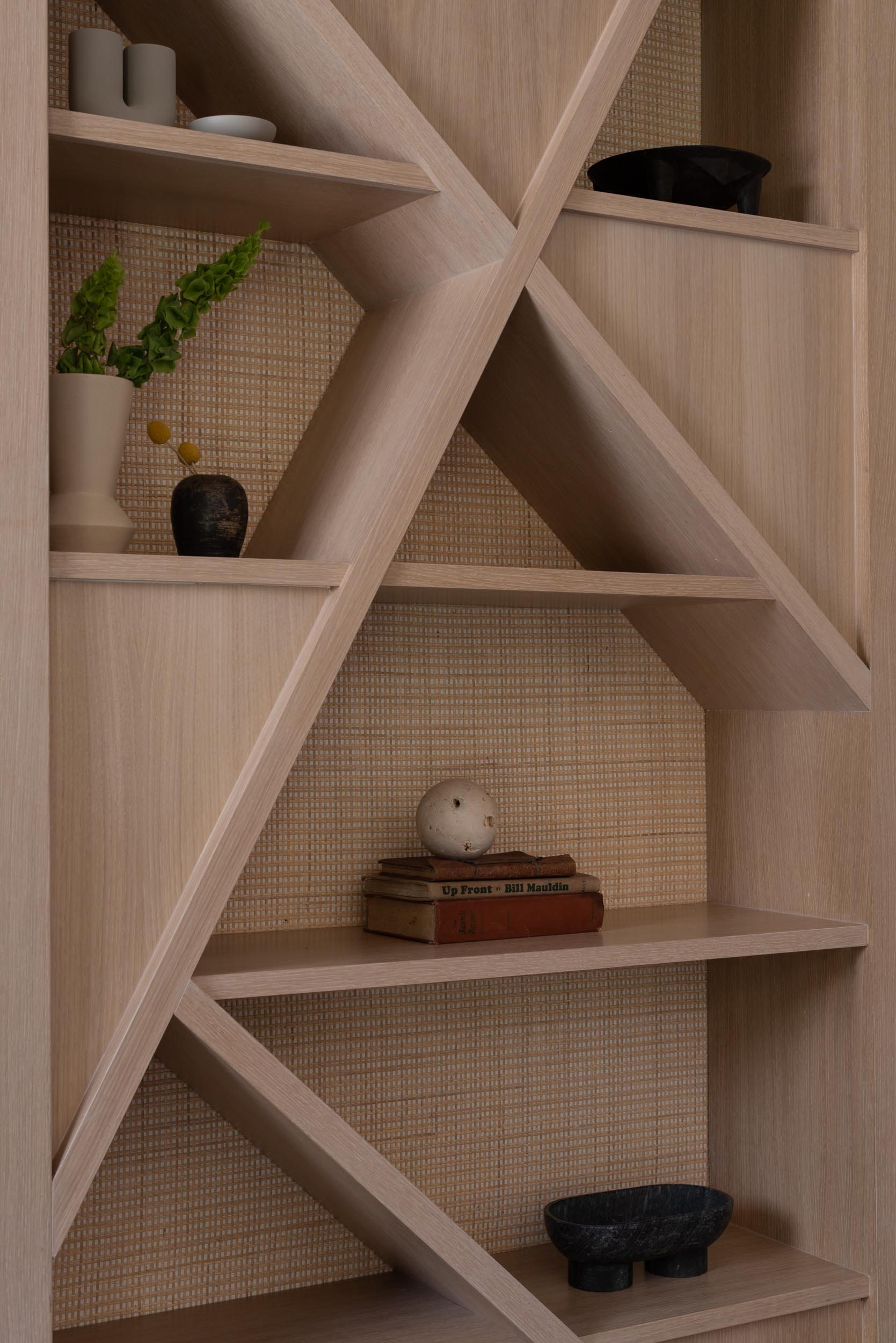 A modern shelving unit with a natural cane backing.