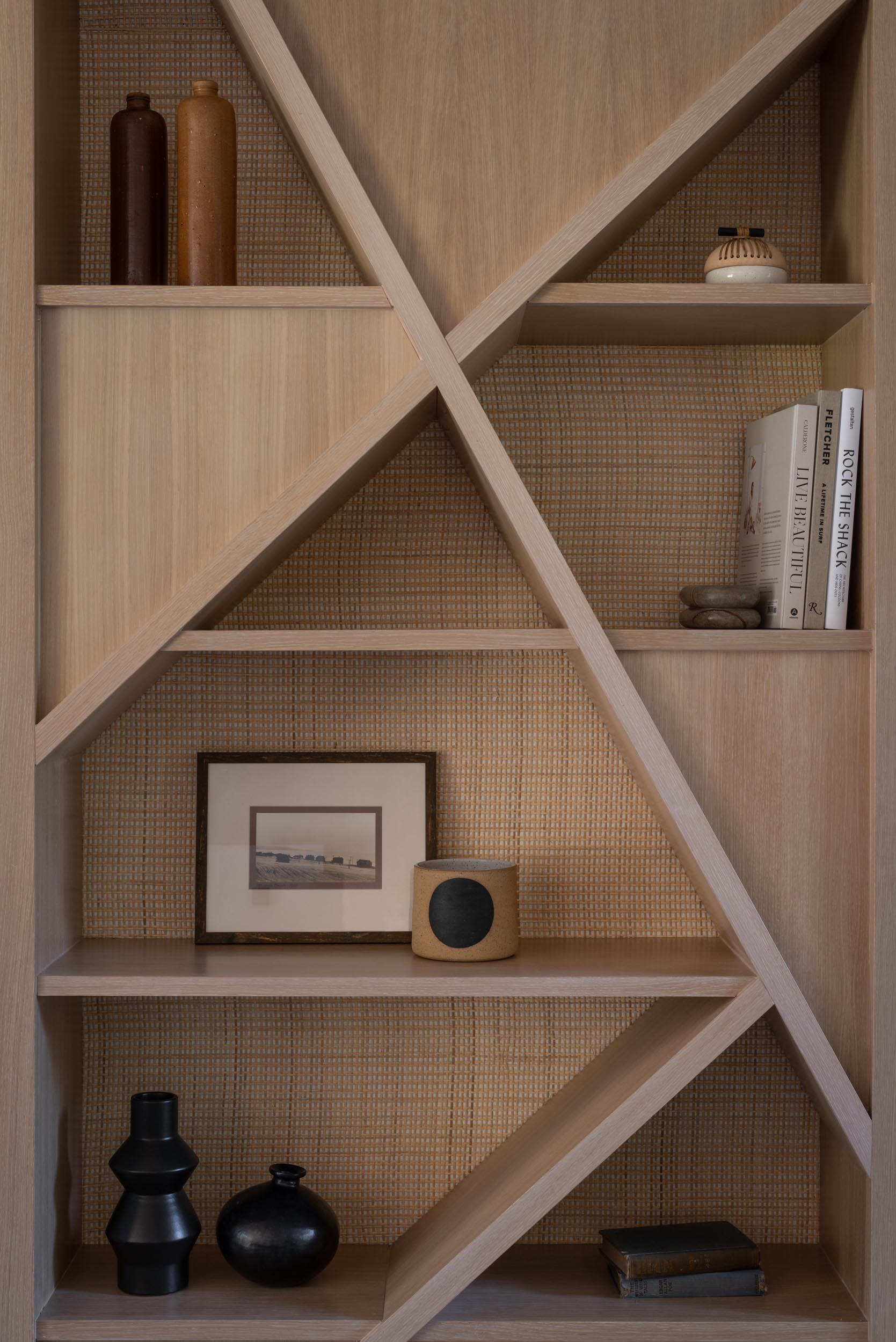 A modern wood shelving unit with a natural cane backing.