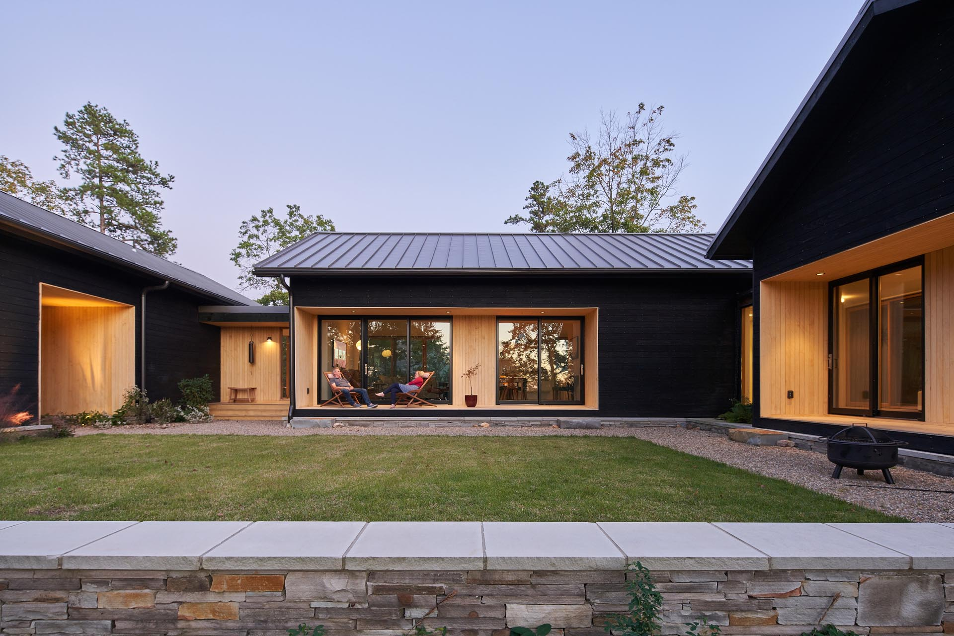 A modern home with burnt wood siding and alcoves lined with contrasting light wood.