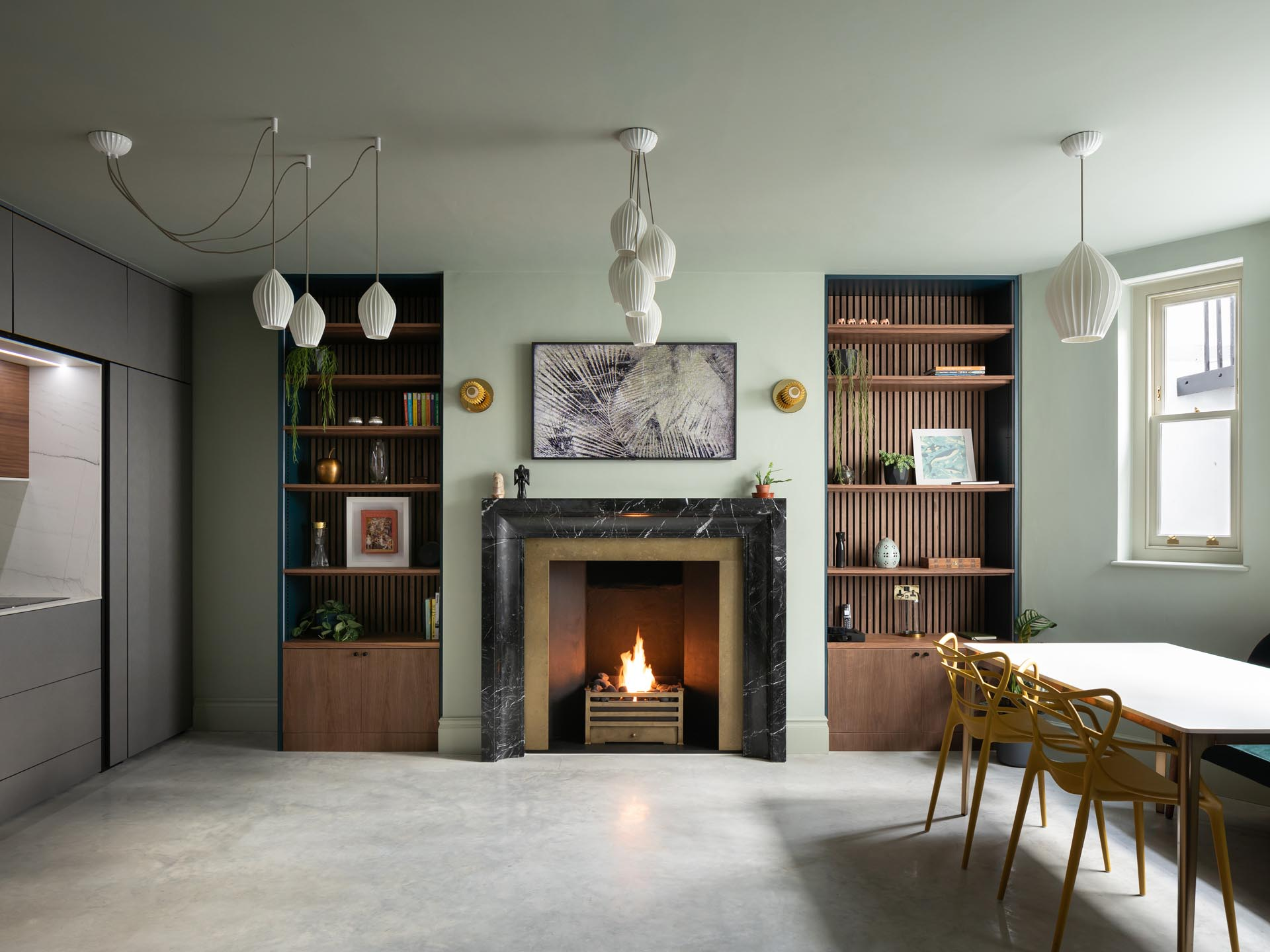 White lighting hangs from the ceiling, while a fireplace is flanked with floor-to-ceiling wood bookshelves.