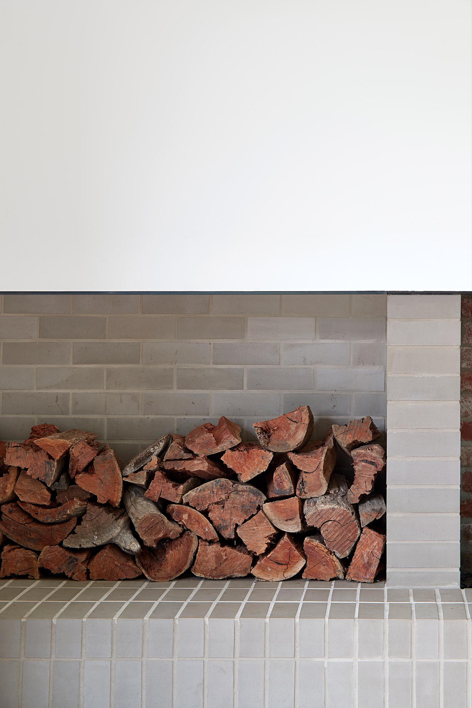 A modern brick fireplace with firewood storage.