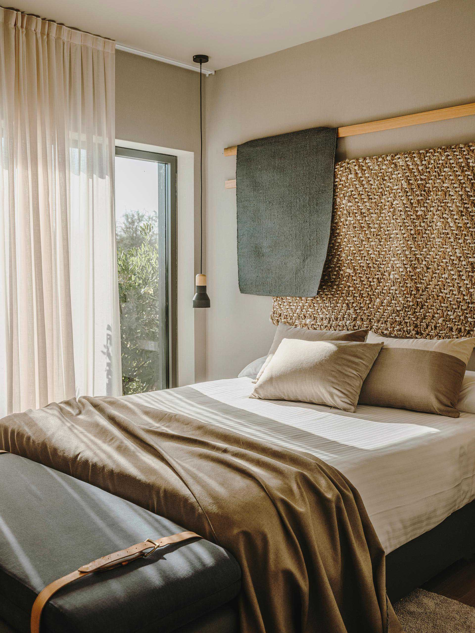 Wood lengths with draped fabric creates a unique wall decor installation in a bedroom
