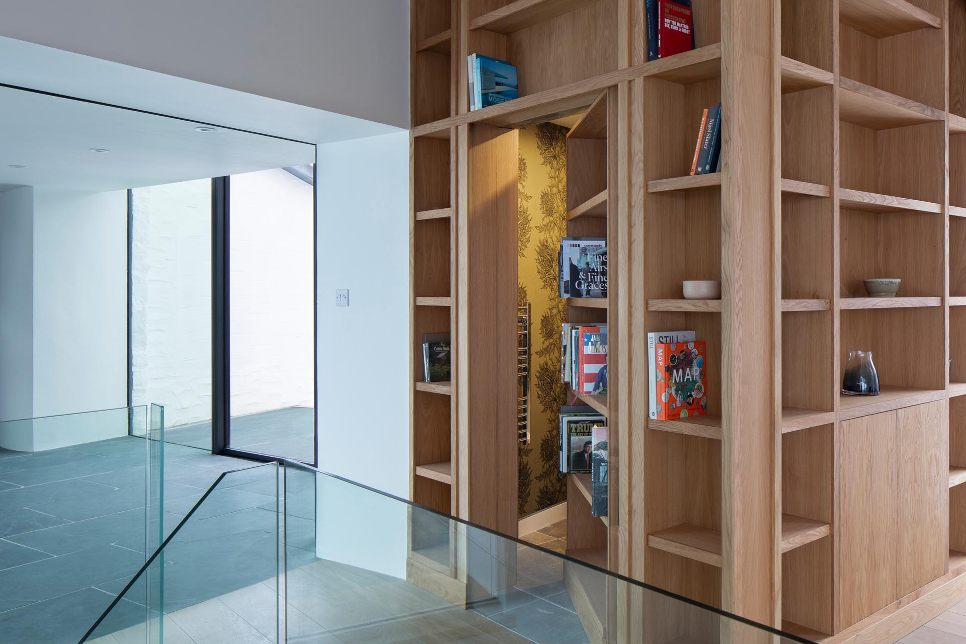 A wood bookshelf hides a powder room.