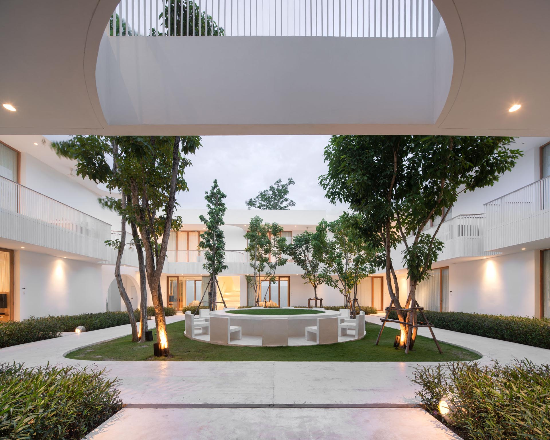 A modern hotel courtyard with outdoor chairs arranged in a circle.