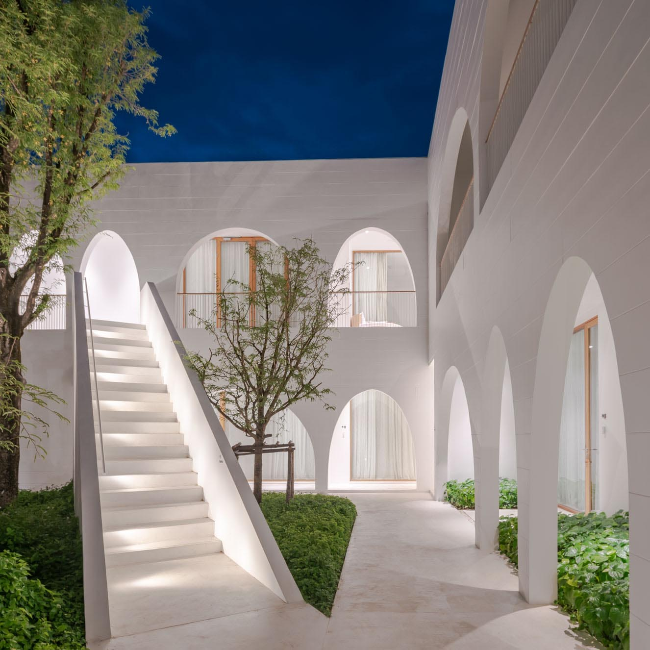 A modern hotel with arches and white stairs with lighting.