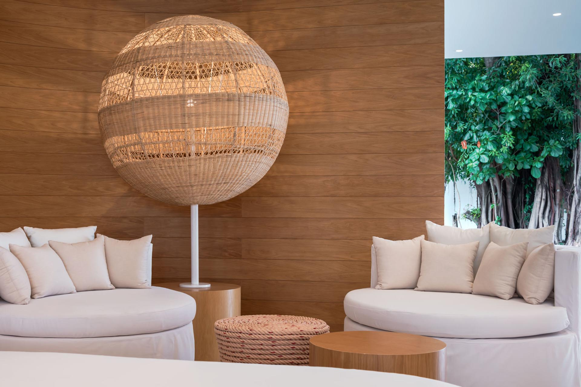 A modern hotel lobby with wood walls, woven lighting, and round furniture.