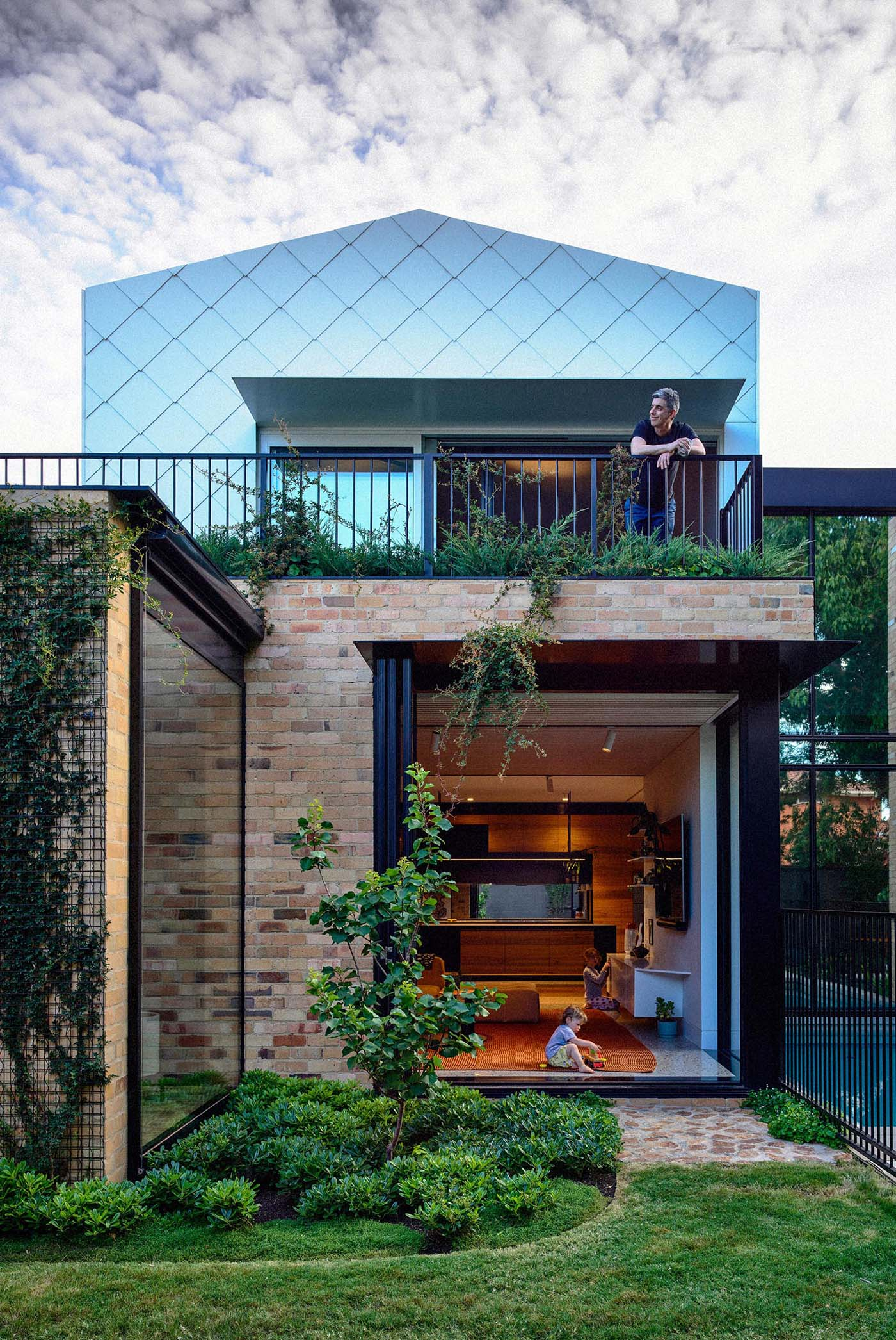A modern home with indoor/outdoor living spaces, has been built using recycled yellow brick and metal shingles.