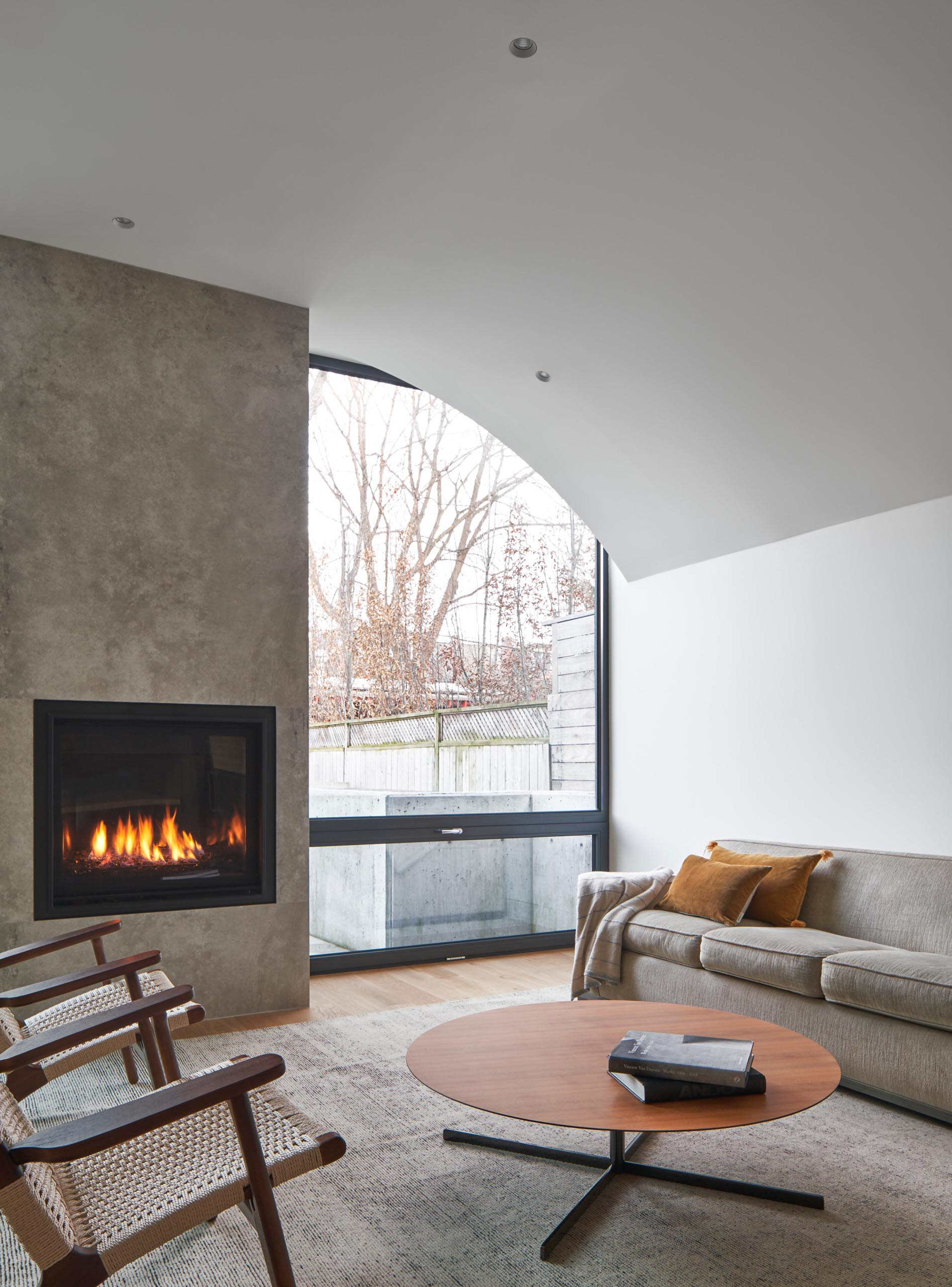 This modern living room, which is located at the rear of the home, has a fireplace and a large window that provides a view of the backyard.