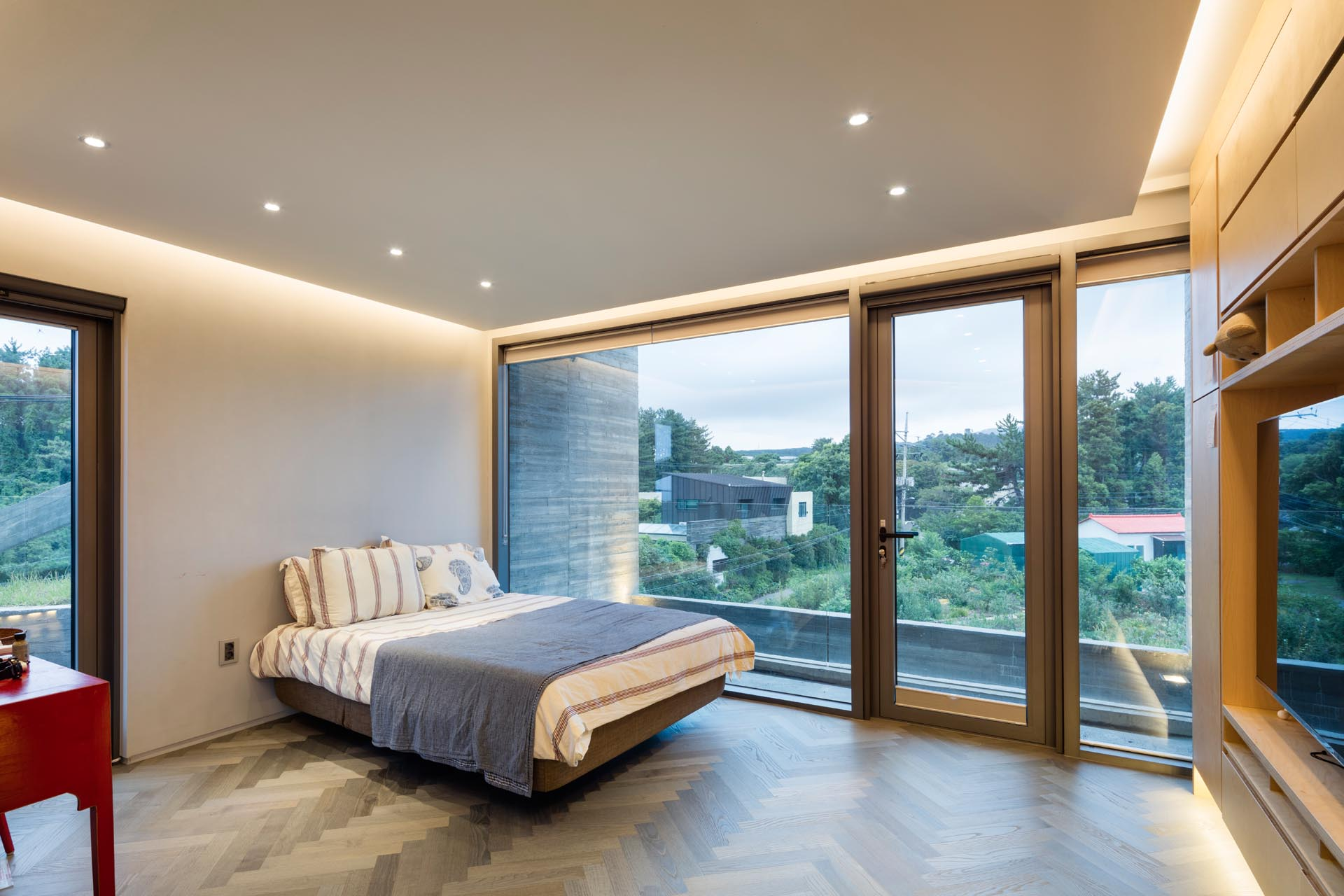 A minimalist bedroom with hidden lighting and large windows.