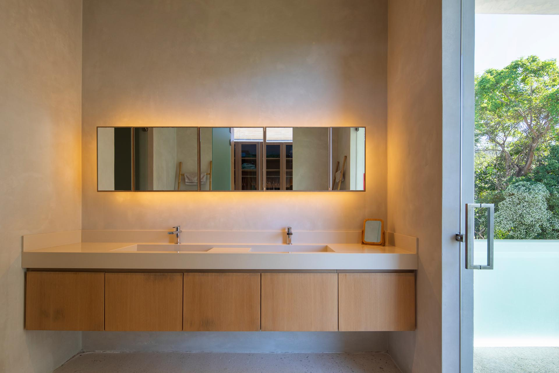 In this modern bathroom a floating wood vanity sits below a horizontal mirror that has a warm glow from the hidden lighting behind it.