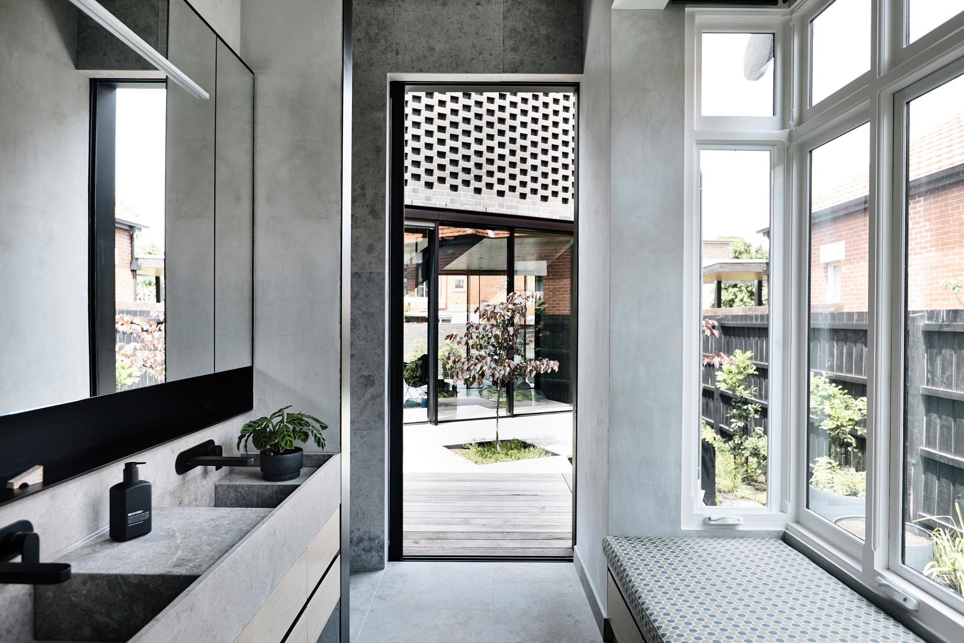 A modern en-suite bathroom that opens to a courtyard.