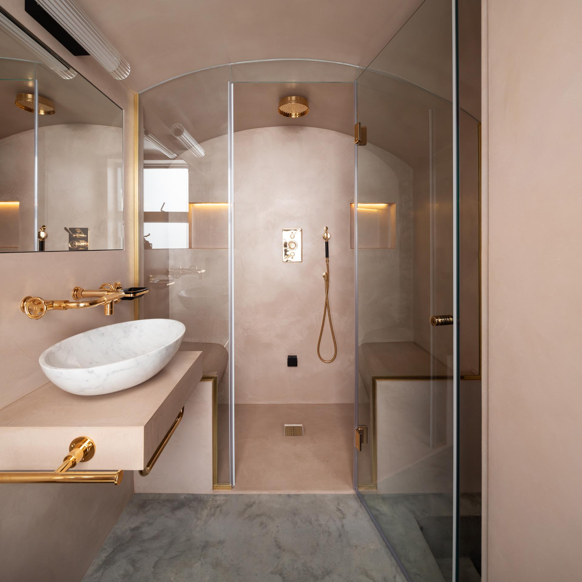 A modern steam room with a curved glass screen, blush pink walls, and rose gold hardware.