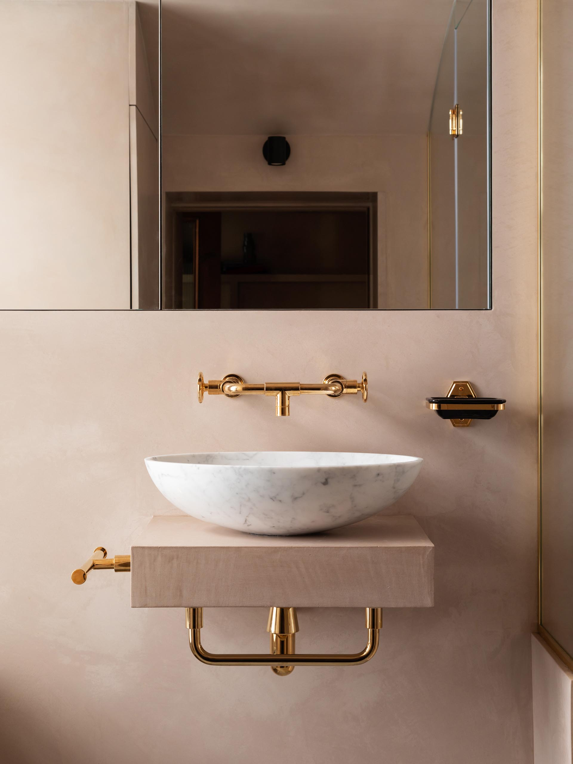 A blush pink bathroom with a marble vessel sink and rose gold hardware.