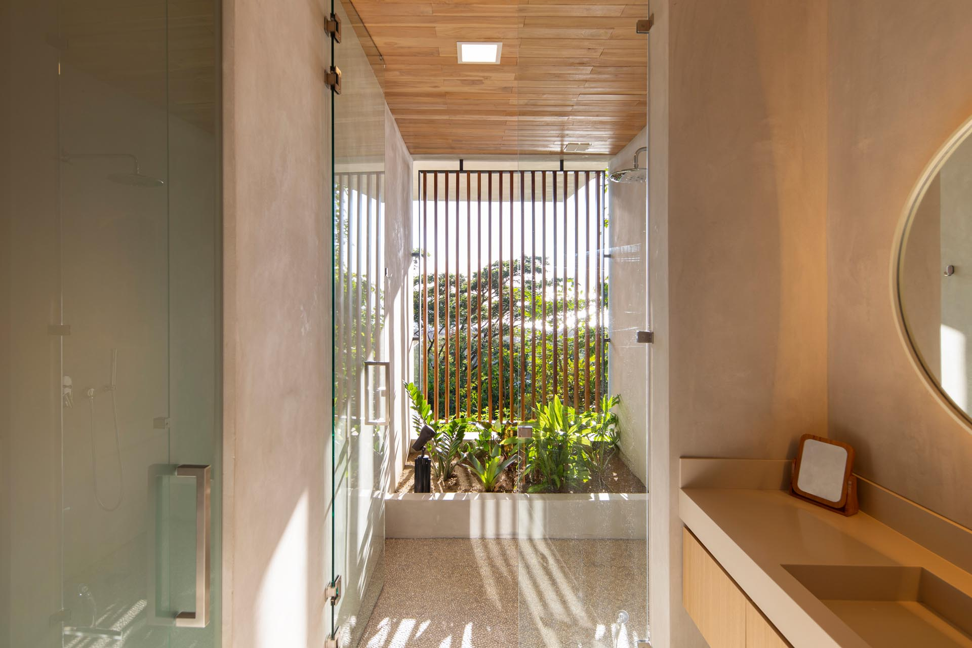 In this modern bathroom, the shower is located in a semi-outdoor room with plants and wood slat screen.