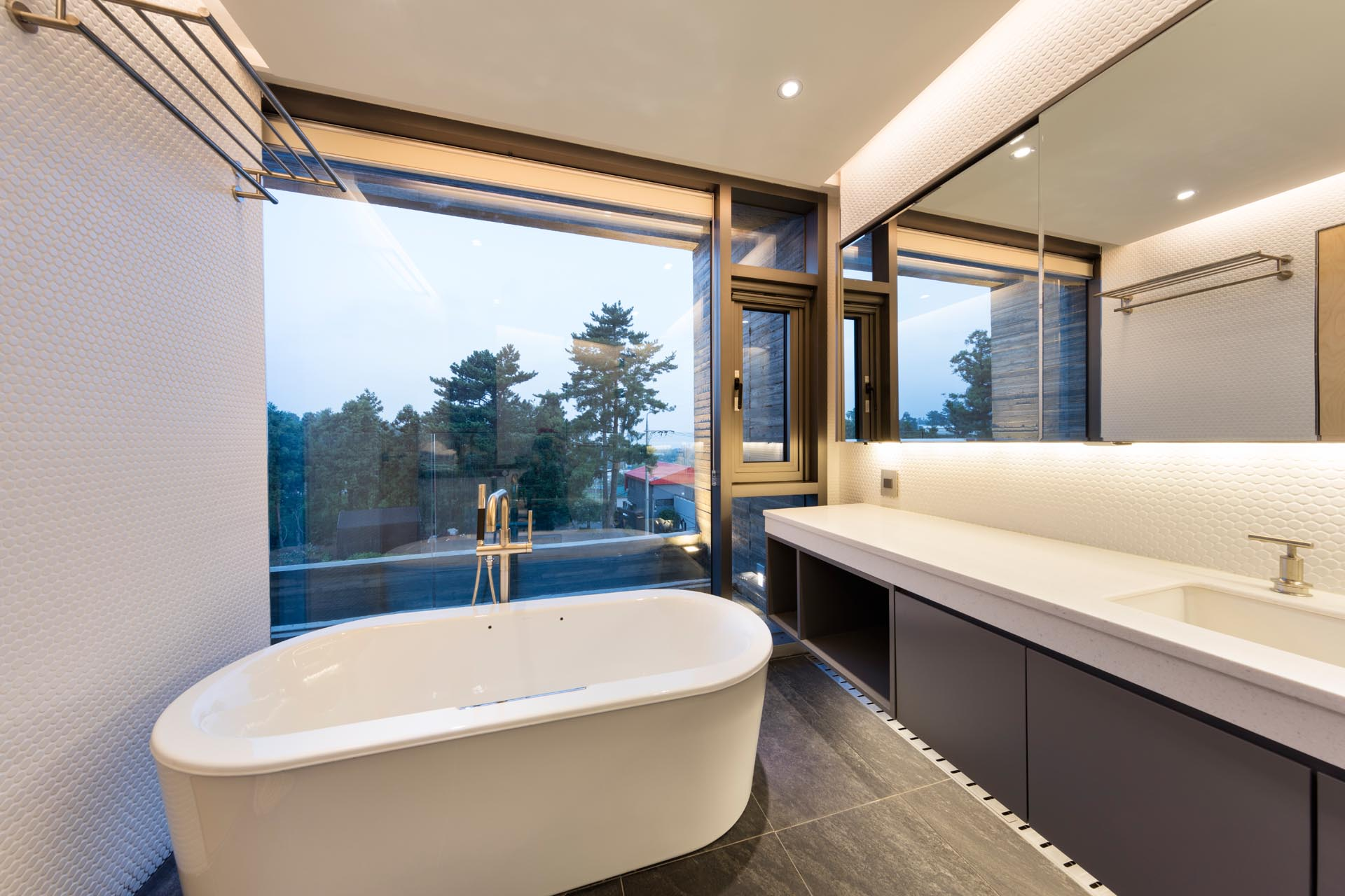 A modern bathroom with a freestanding bathtub and a large picture window.