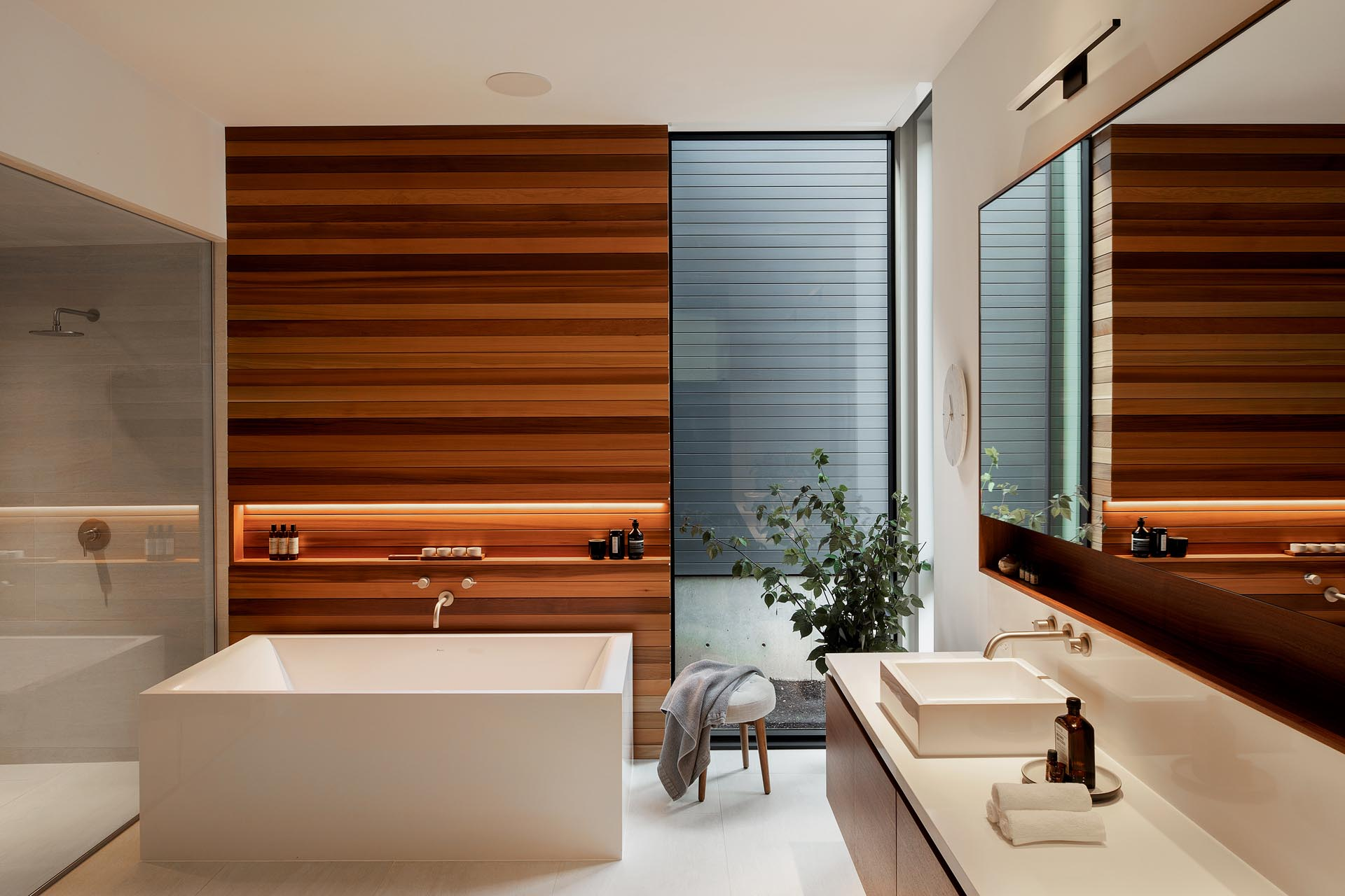 This en-suite bathroom has a warm wood accent wall with varying tones, and includes a horizontal shelving niche with hidden lighting.