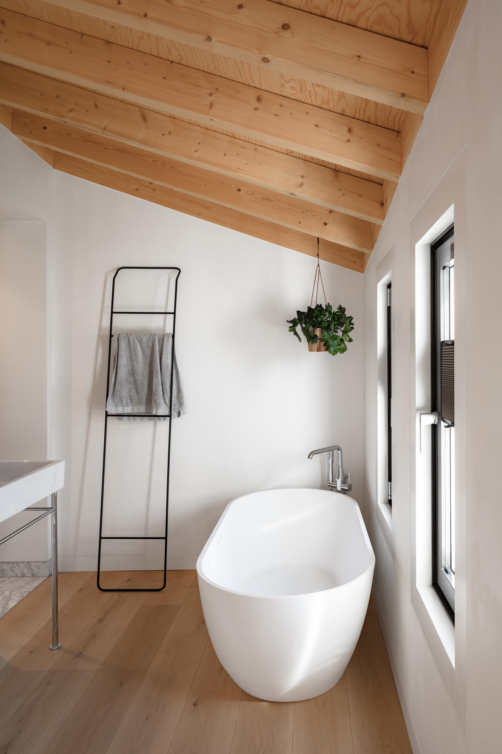 A modern bathroom with an  exposed wood ceiling that complements the wood floor, while the hanging planter in the corner adds a touch of nature.