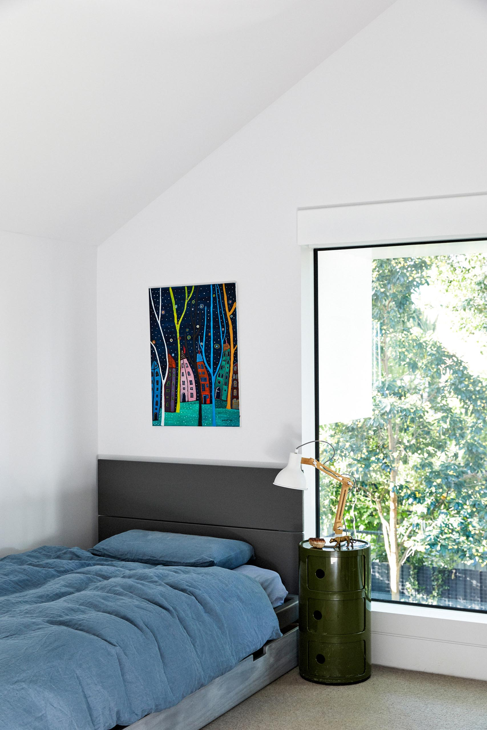 In this modern bedroom, bright white walls create a clean and crisp look, while the artwork adds a touch of color.