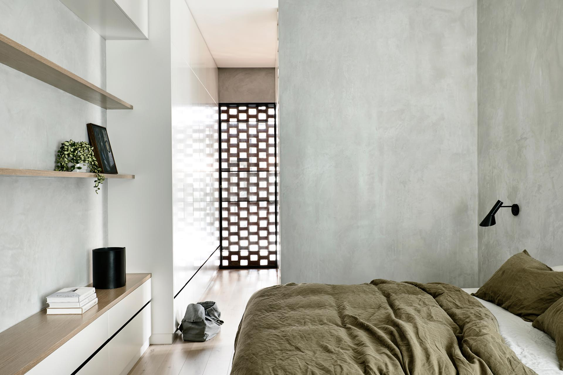 A simple yet modern bedroom design that takes advantage of the light through the brickwork at the end of the closet.
