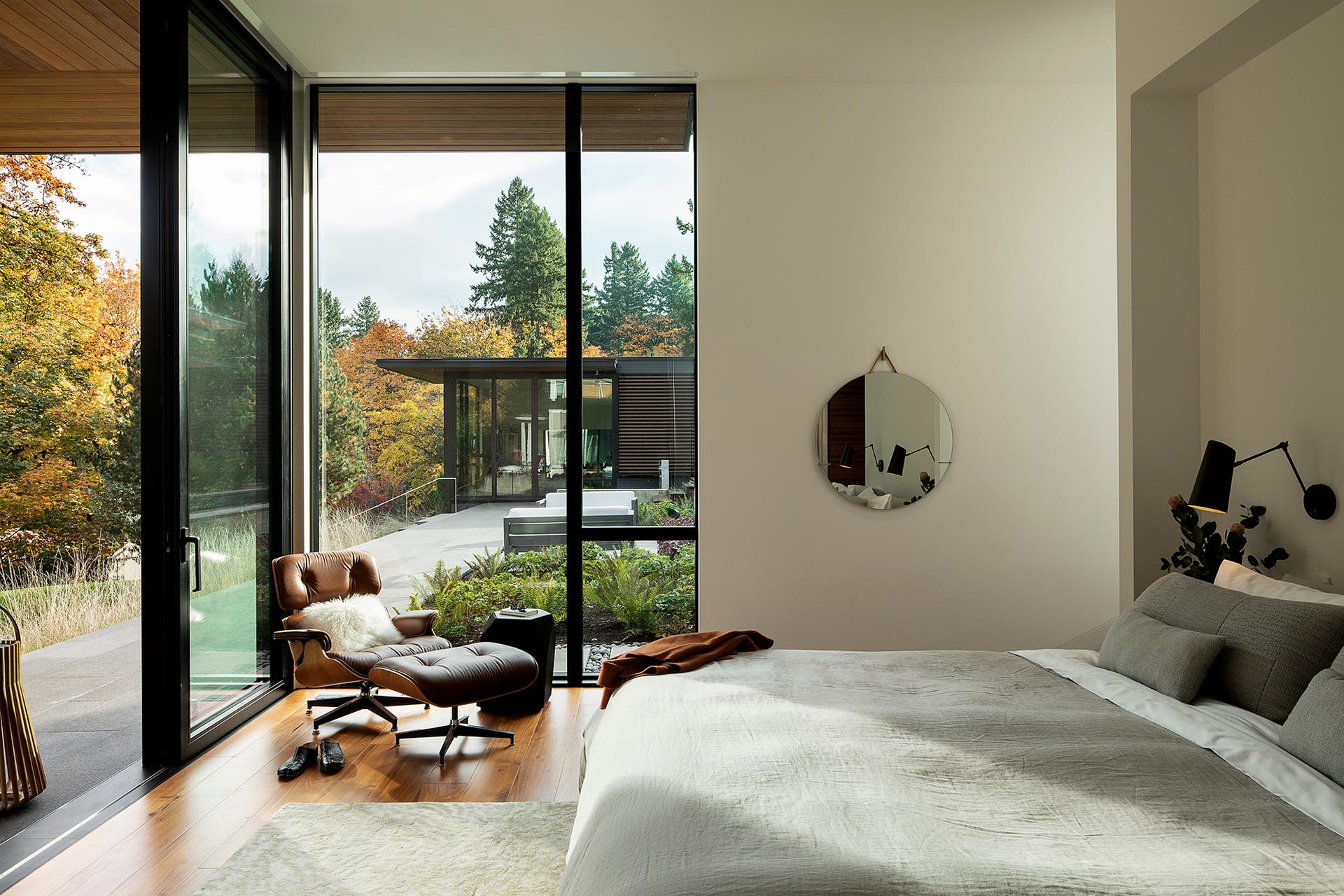 A modern bedroom with large windows and a door that opens to a terrace.
