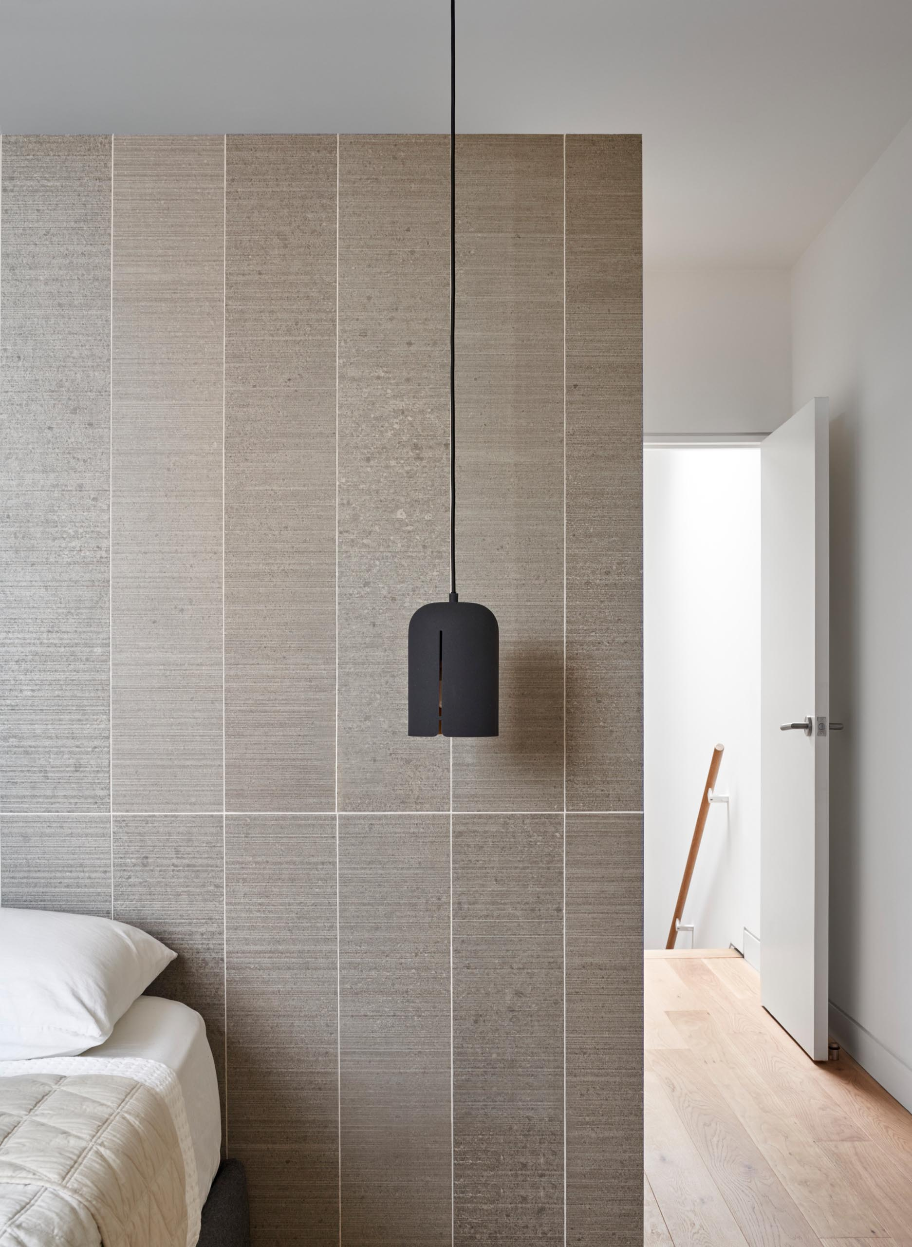 In this bedroom, a matte black pendant light contrasts the accent wall behind the bed and acts as a bedside lamp.