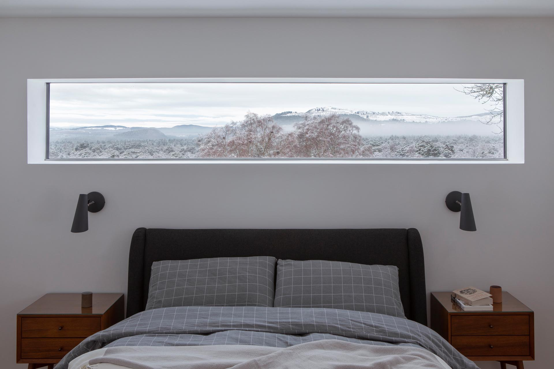 In this modern bedroom, a thin horizontal window removes the need for artwork, as it perfectly frames the view.