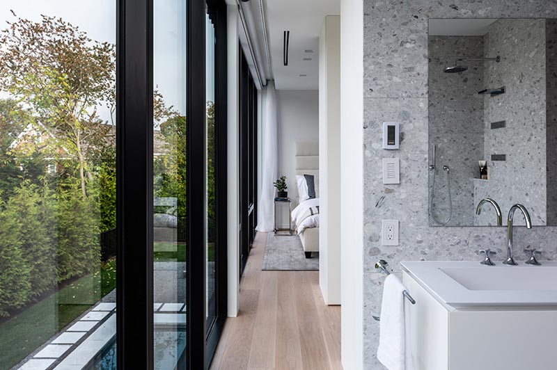 Black-framed windows contrast the light interior of the primary bedroom and en-suite bathroom.