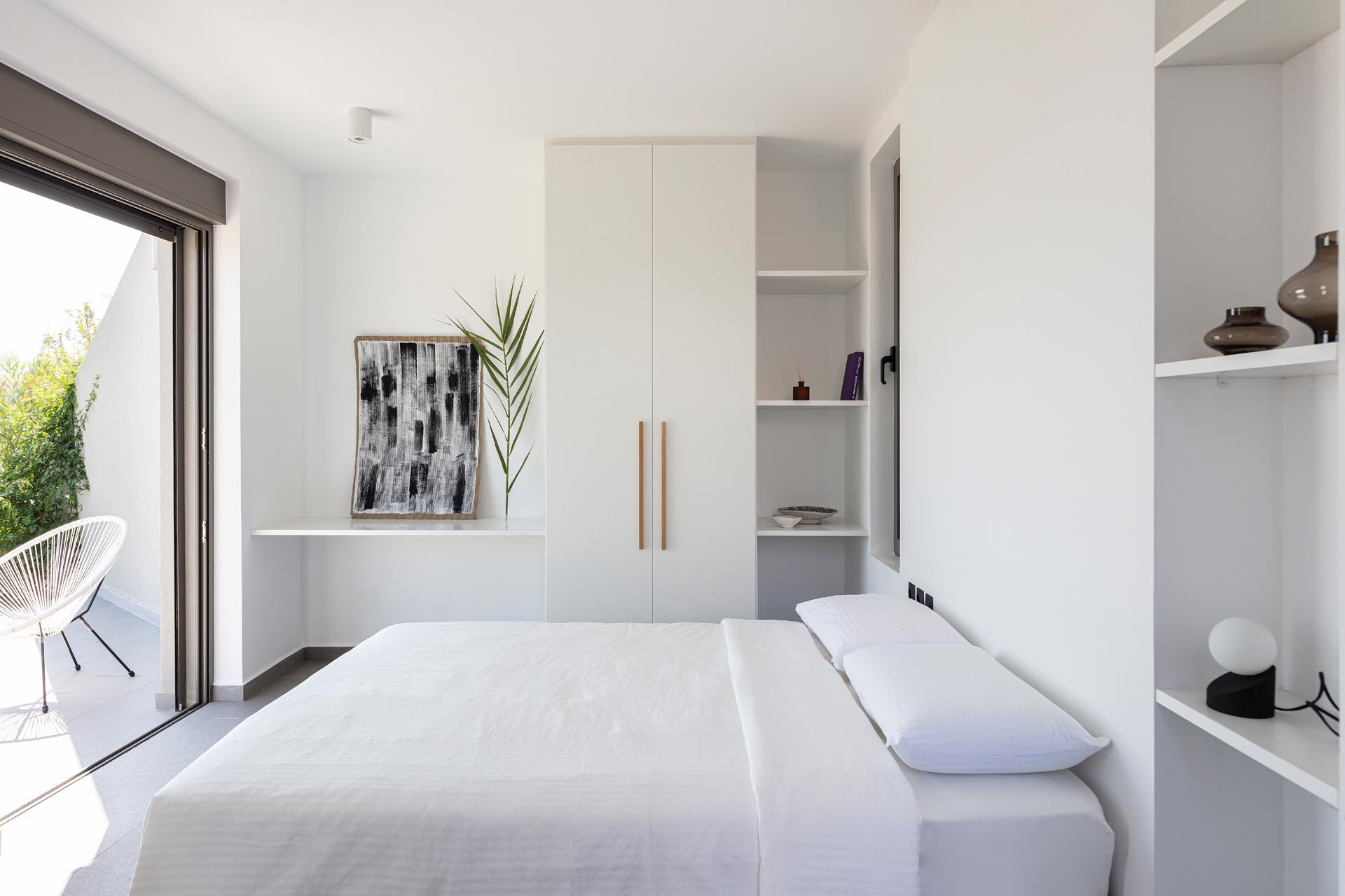 A modern white bedroom with built-in shelves and closets.