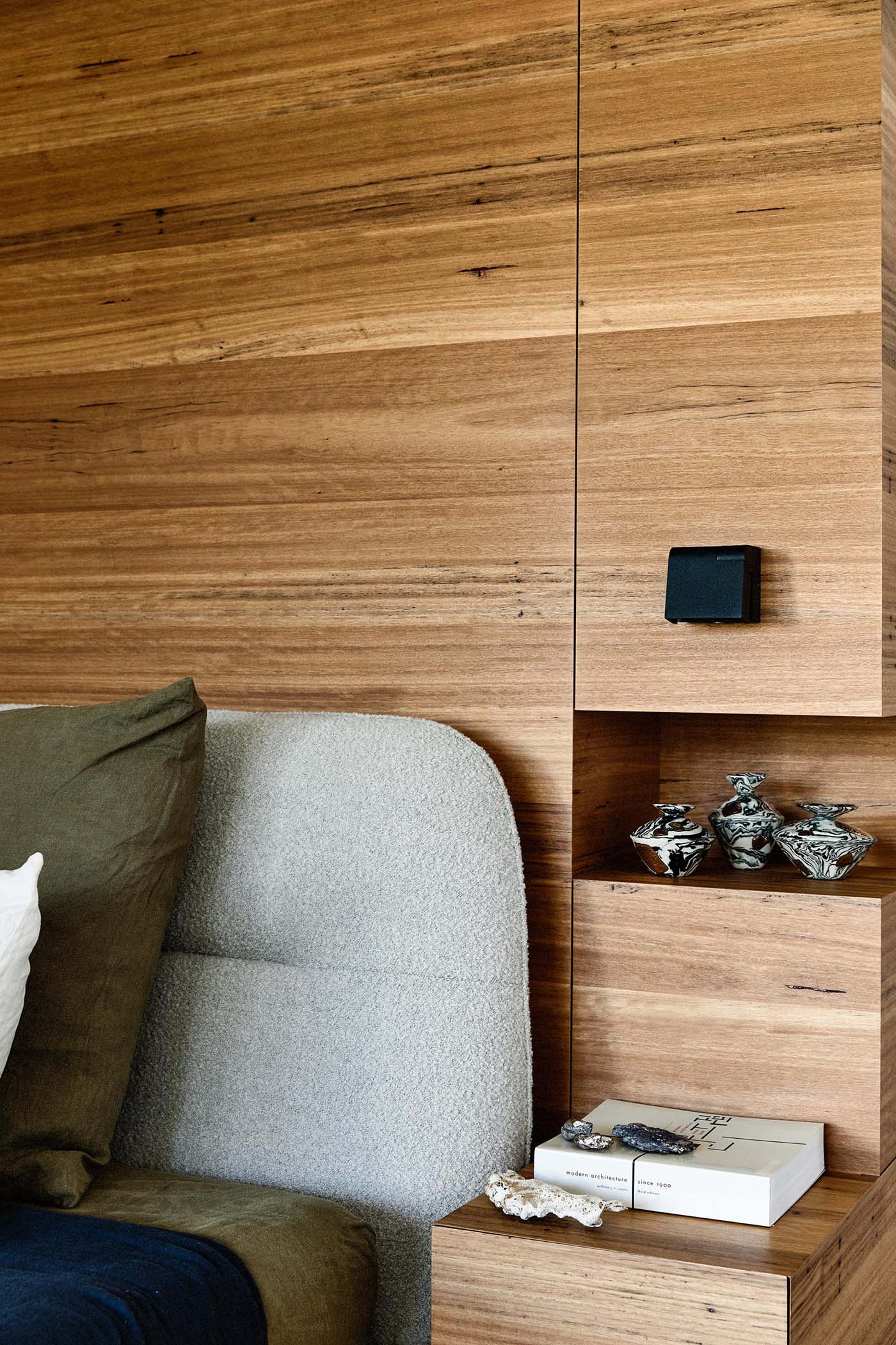 In this modern bedroom, a partial wood wall becomes the backdrop for the bed, and includes bedside tables and shelving niches in its design.